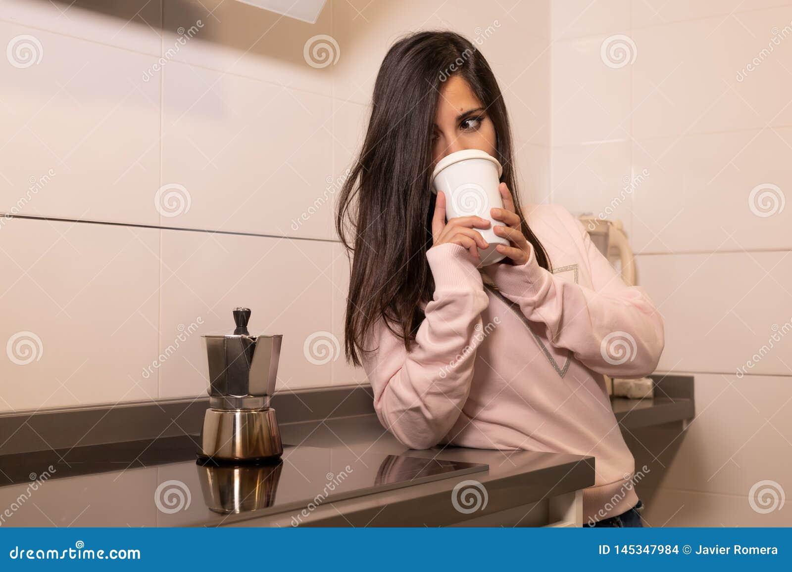 Café bebendo da menina em sua cozinha