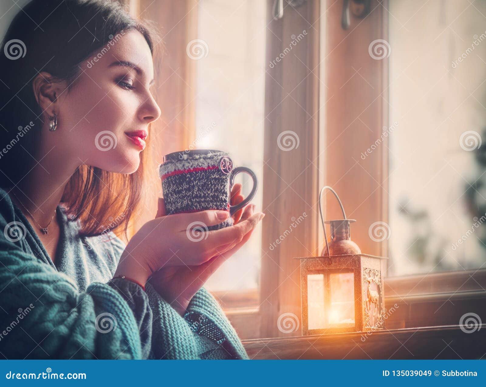 Café bebendo da menina moreno bonita em casa, olhando para fora a janela Mulher do modelo da beleza com o copo do chá quente