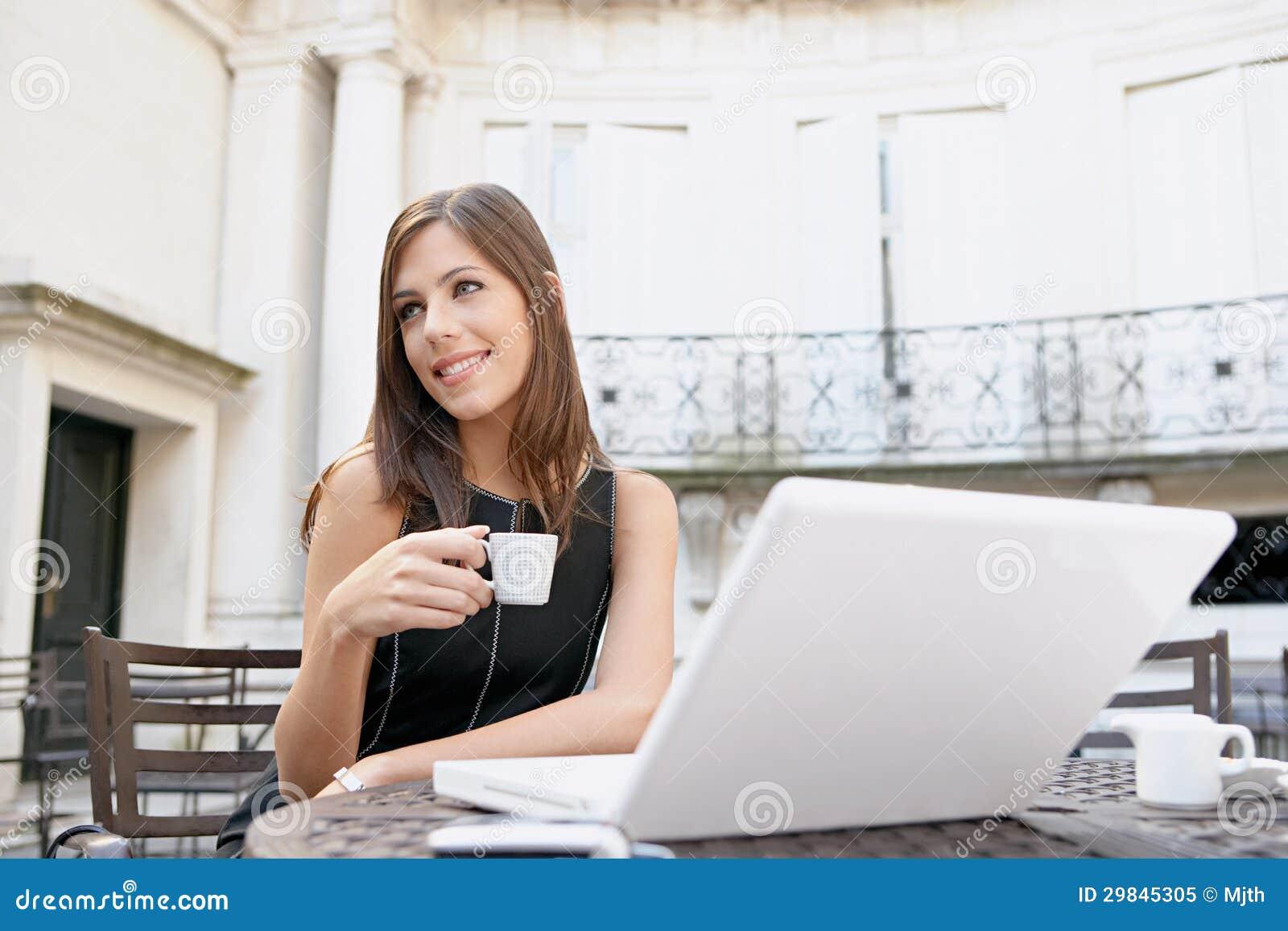 Café bebendo da mulher de negócios com portátil