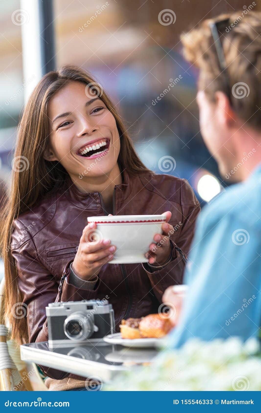 Café bebendo da mulher feliz no café Menina asiática, conversação com assento de riso do amigo do homem na tabela do restaurante