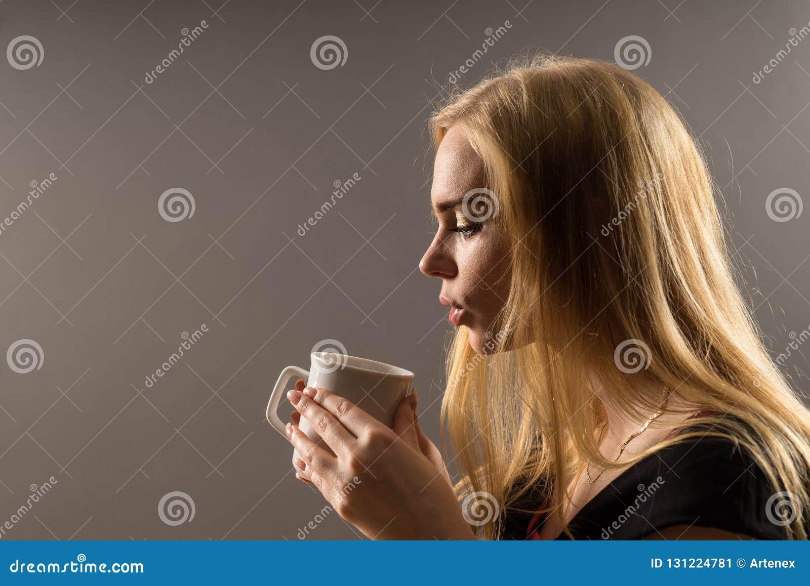 Café bebendo da mulher nova Menina loura com o copo de chá branco em um fundo cinzento