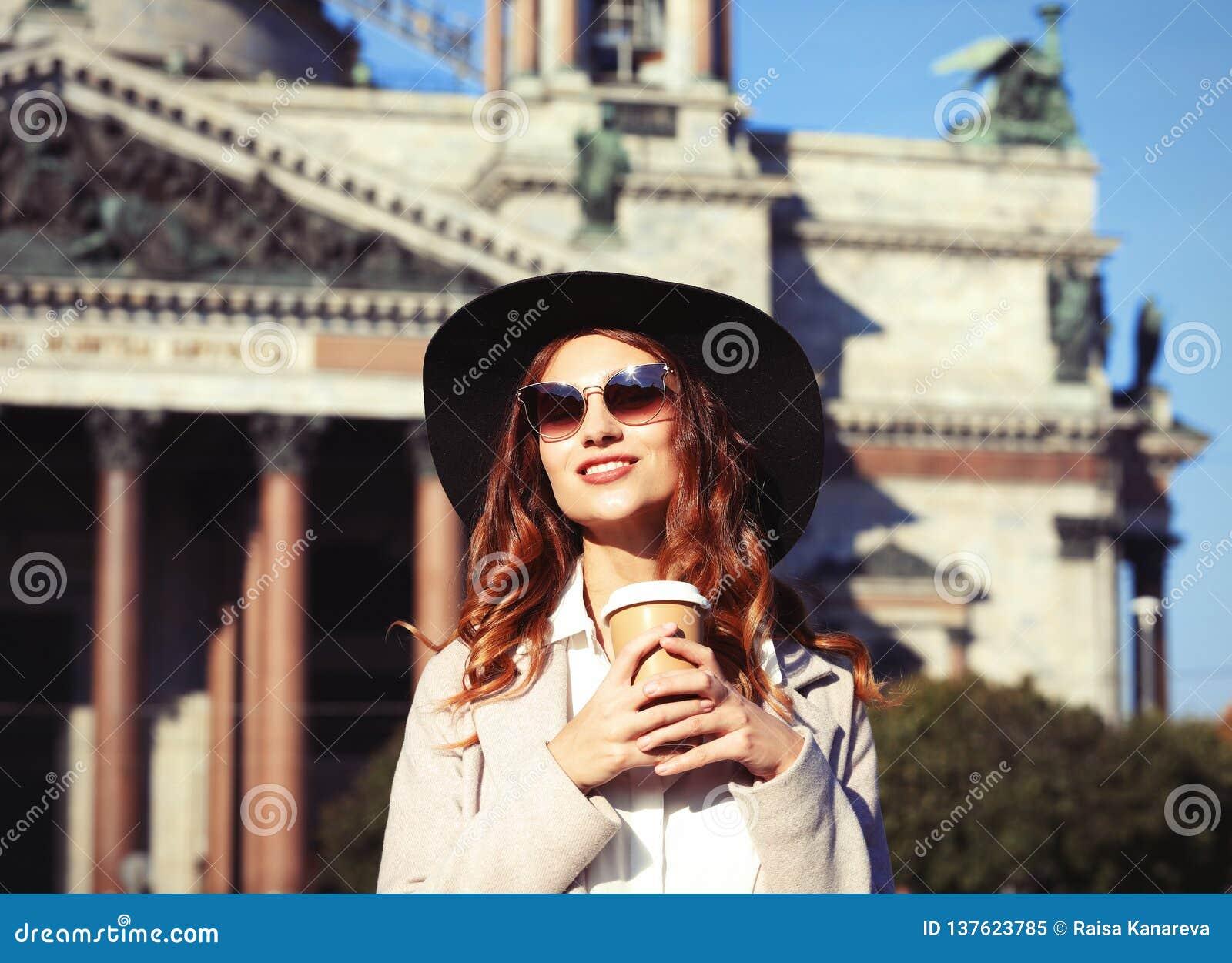 Café bebendo de sorriso da jovem mulher à moda ao andar em uma rua da cidade