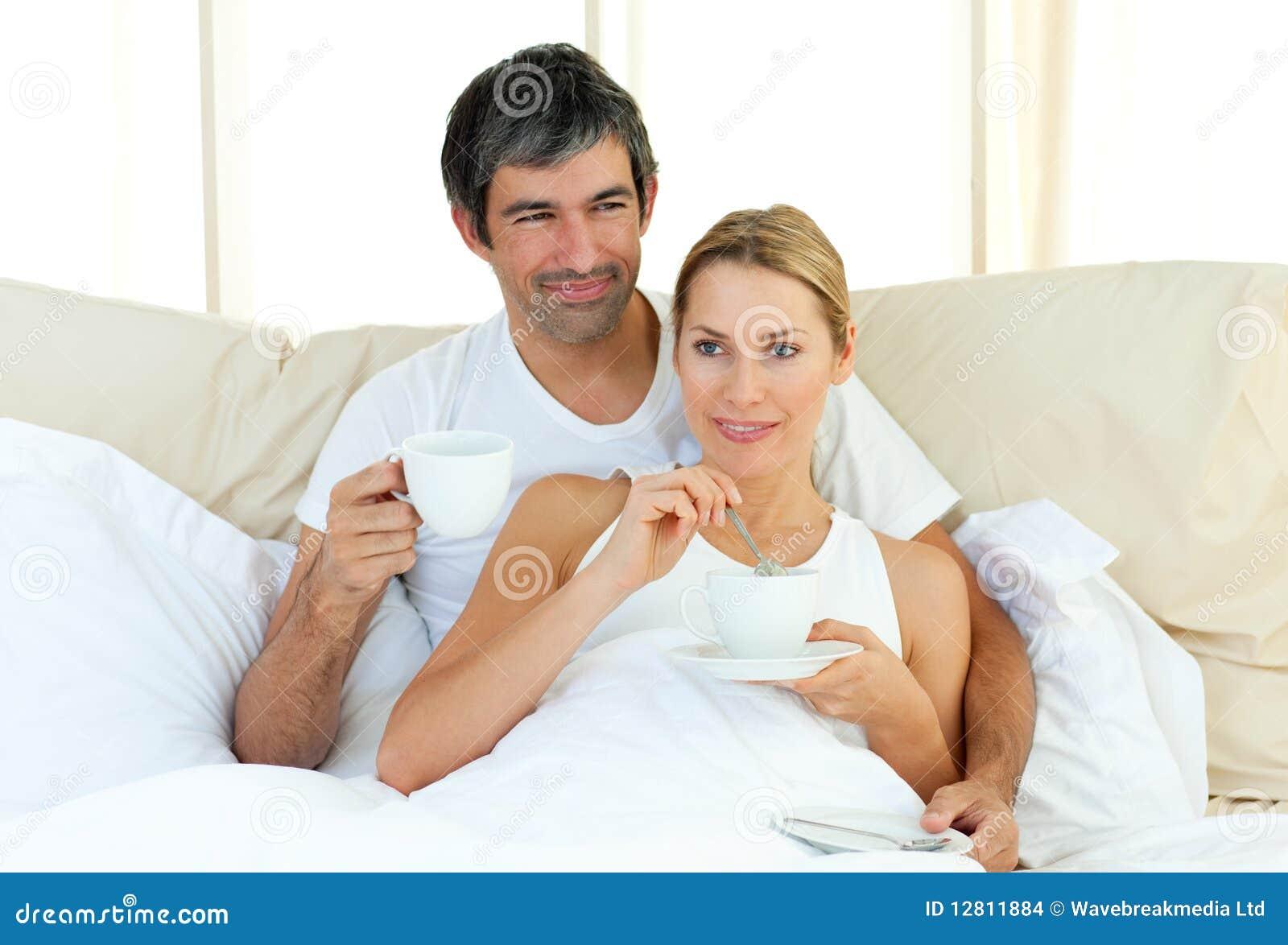 Café bebendo dos pares felizes que encontra-se na cama