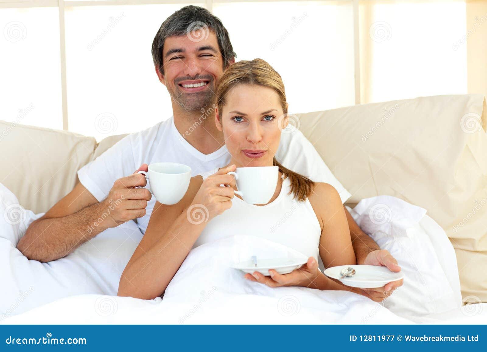Café bebendo dos pares Intimate que encontra-se na cama