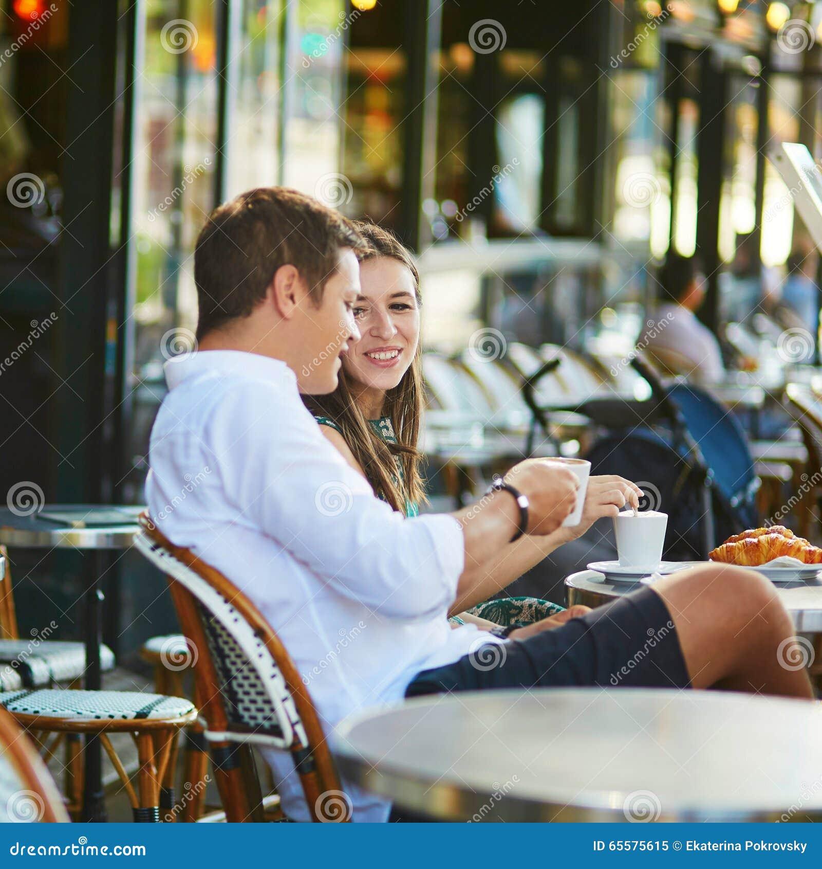 Café bebendo dos pares românticos novos em Paris, França