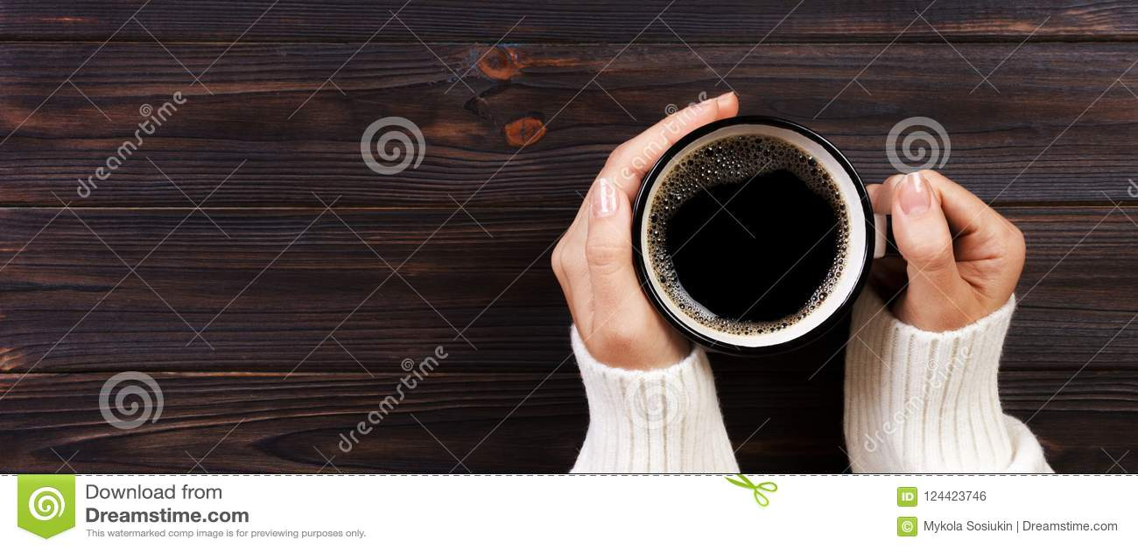 Café bebendo na manhã, ideia superior da mulher só das mãos fêmeas que guardam o copo da bebida quente na mesa de madeira bandeir