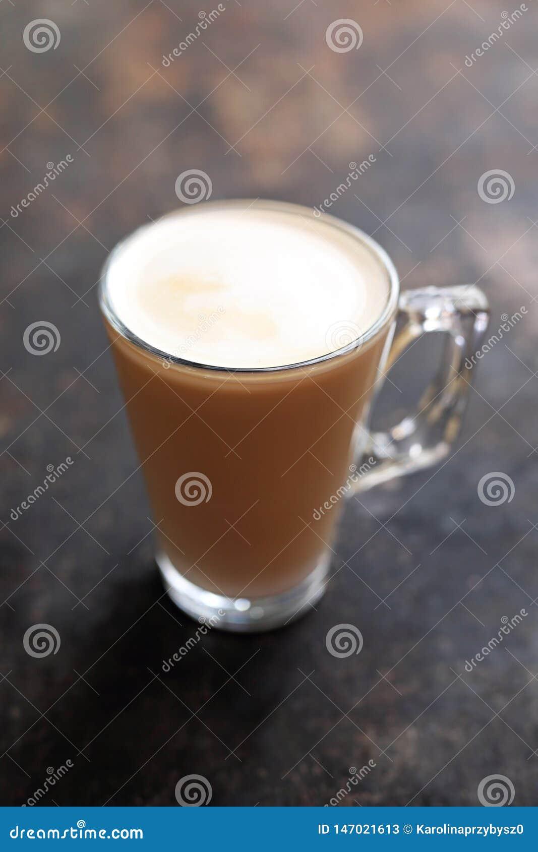 Café blanc plat avec la tasse en verre transparente de mousse de lait