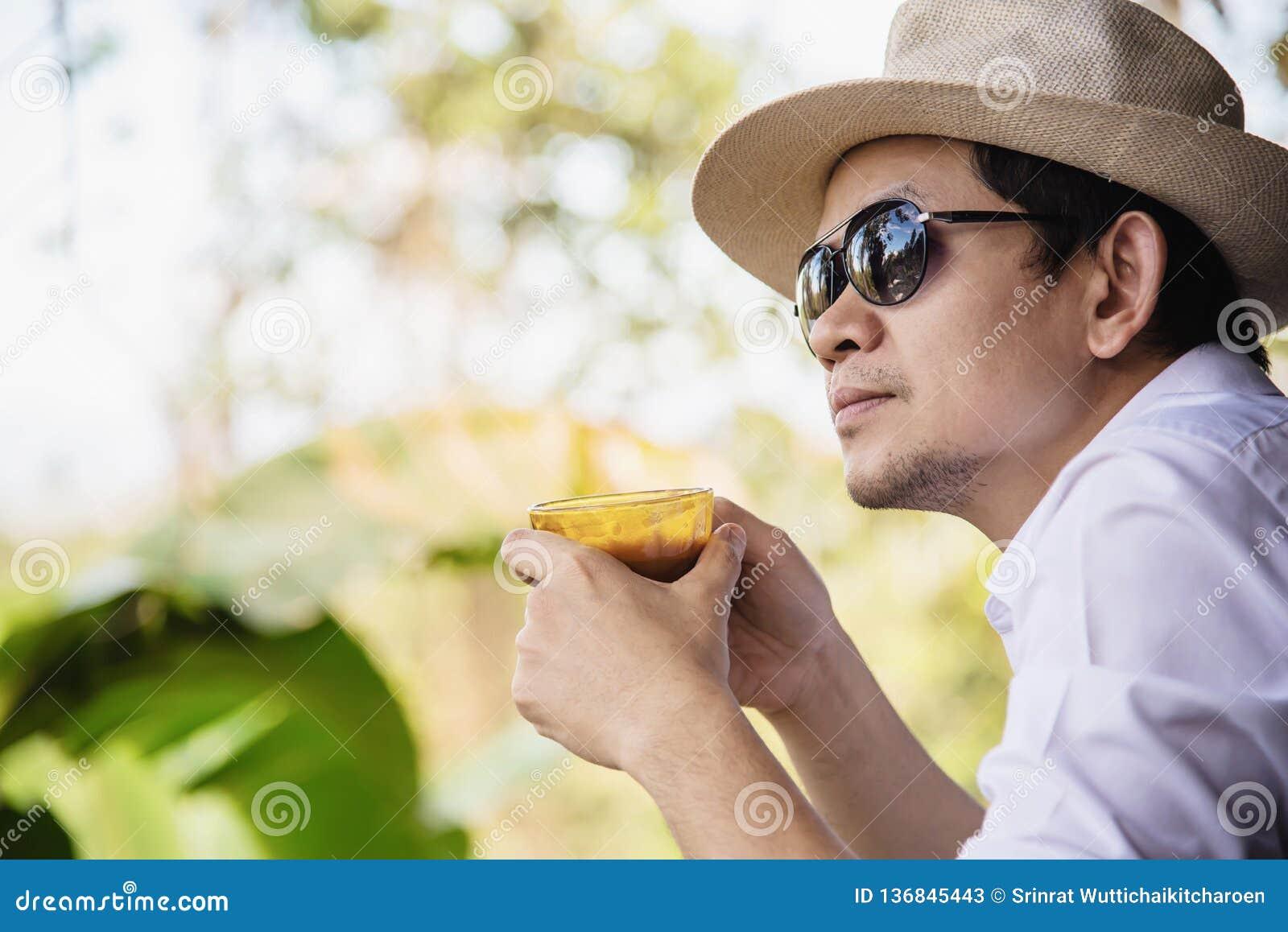 Café caliente de la bebida asiática casual del hombre feliz en naturaleza