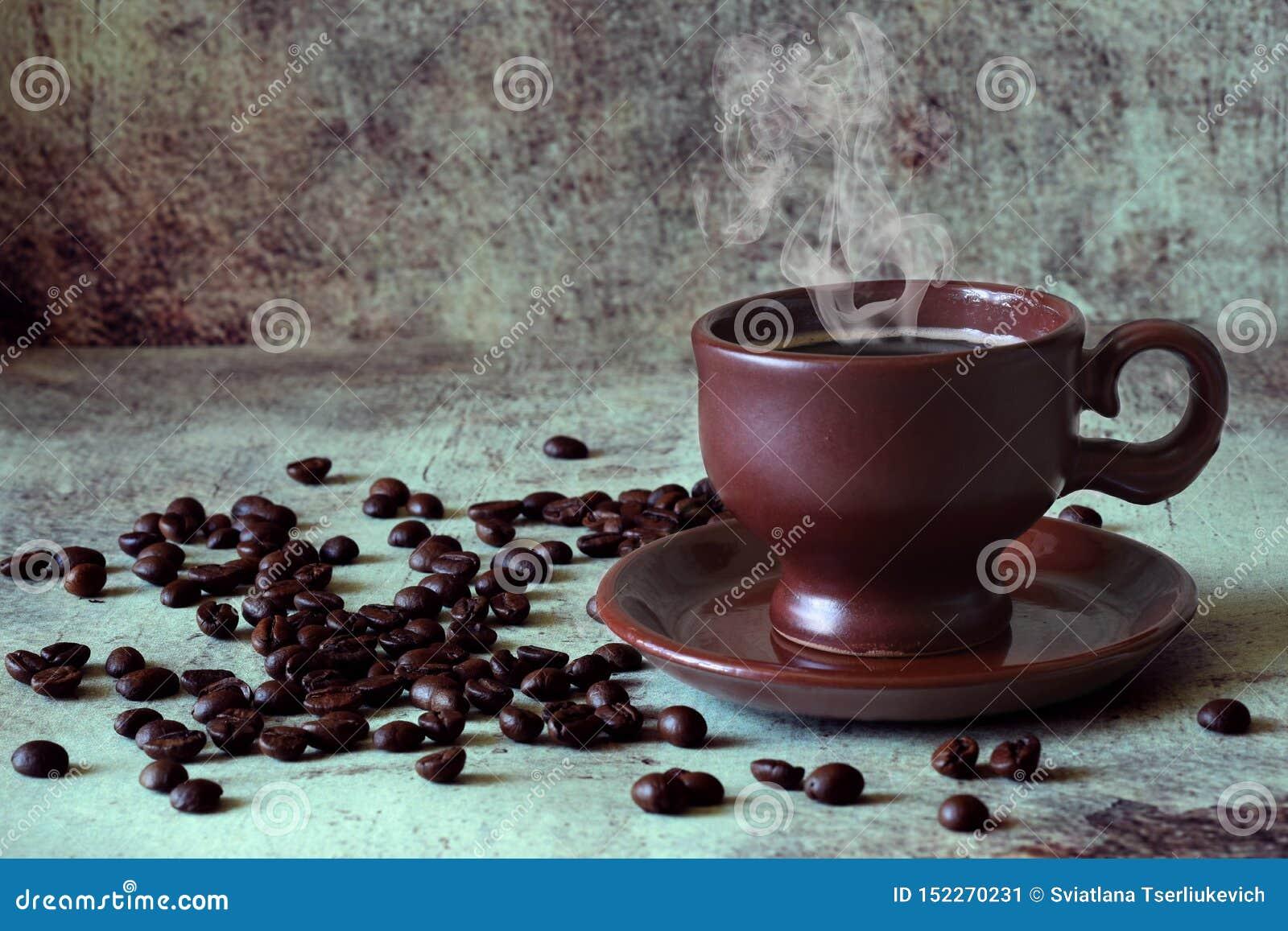 Café caliente fragante en una taza hermosa de la arcilla entre los granos de café dispersados