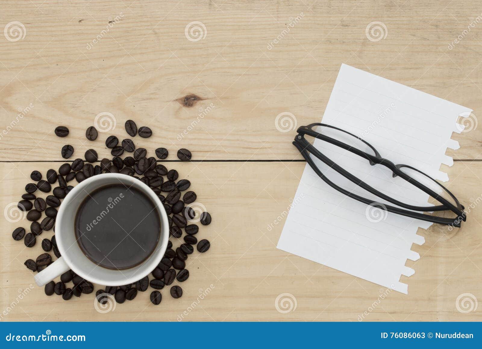 Café, carnet et verres sur la table en bois