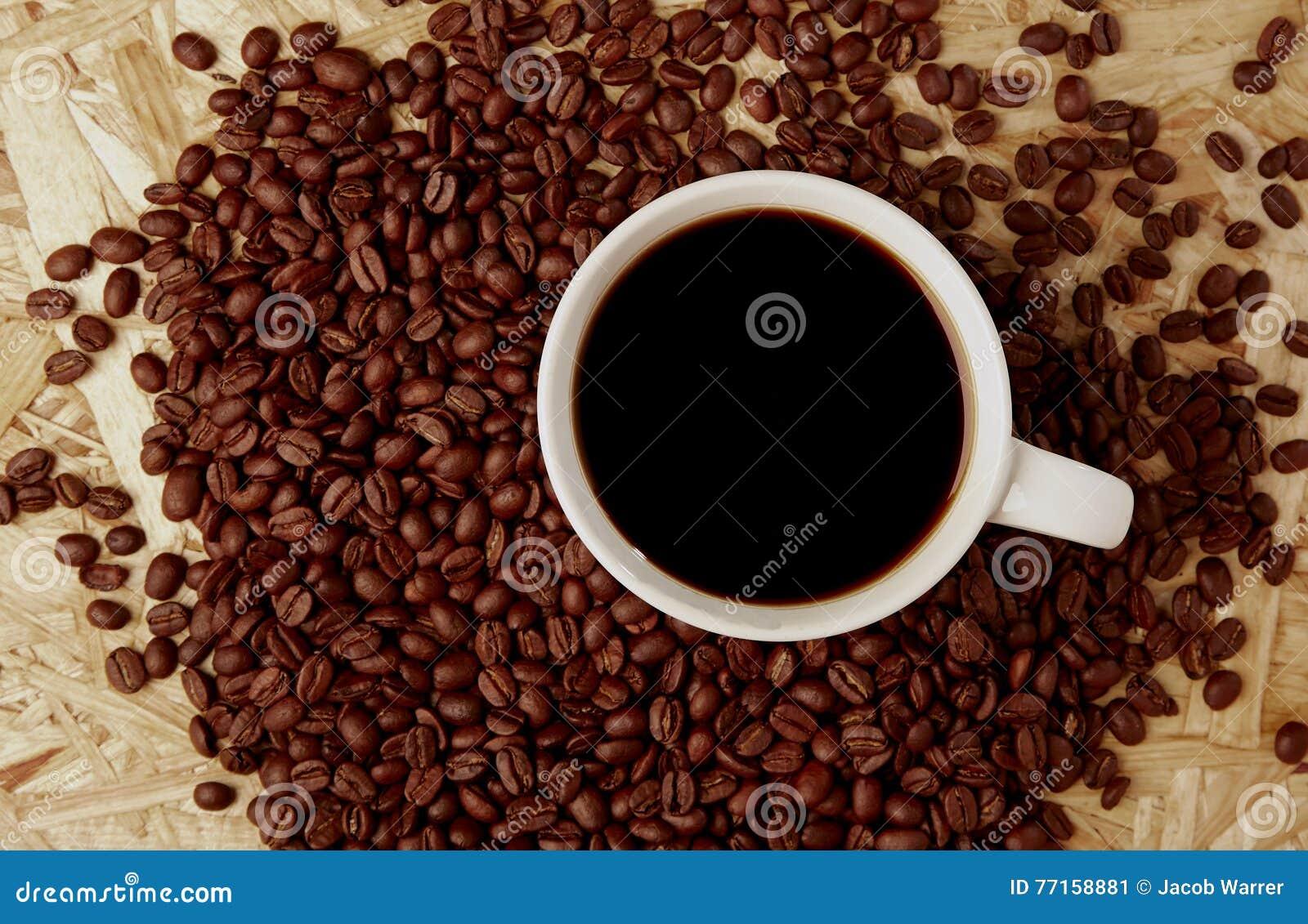 Café chaud avec des haricots sur la texture en bois