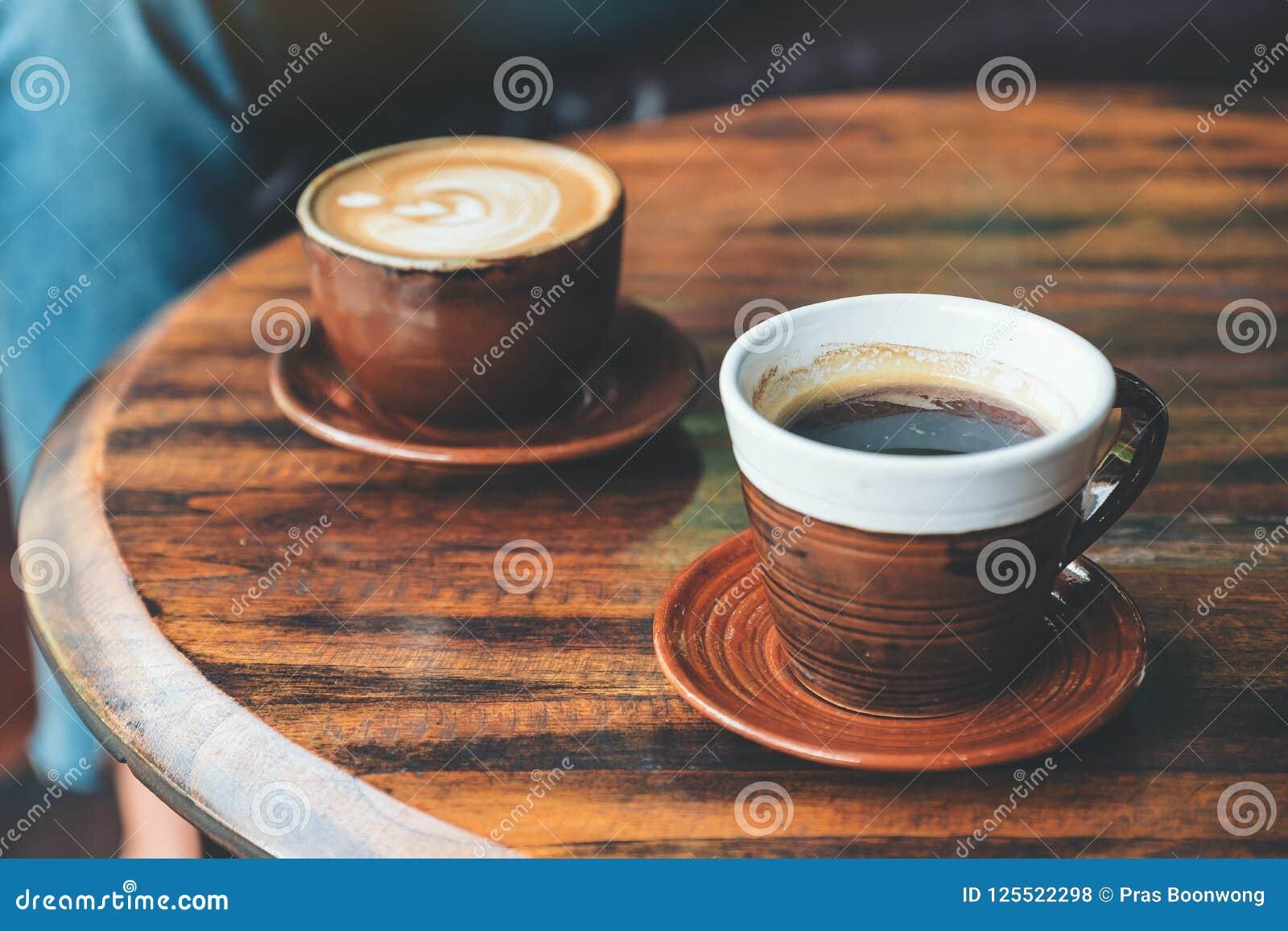 Café chaud de latte et café noir sur la table en bois de vintage en café