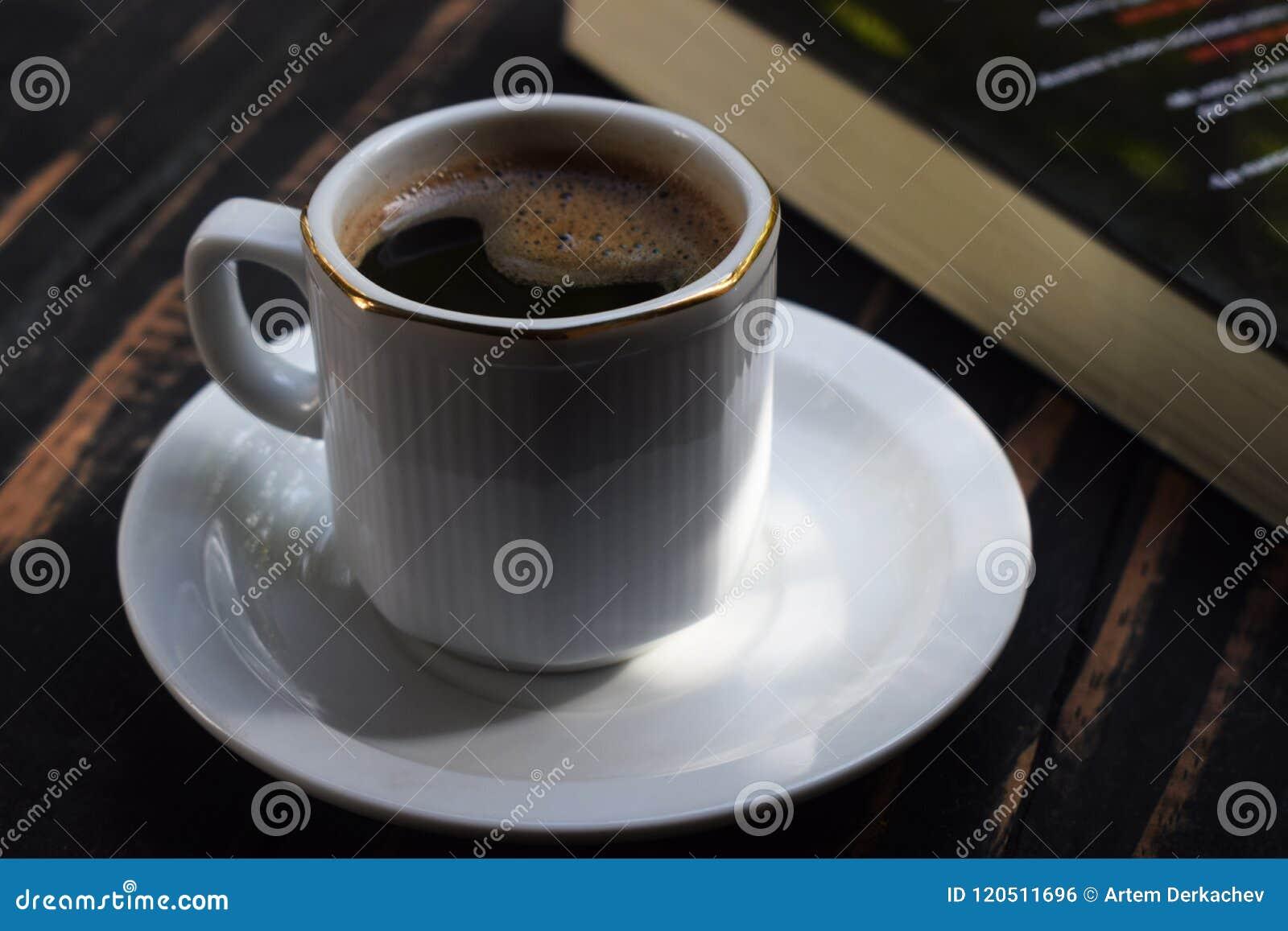 Café chaud de matin sur la table près du livre