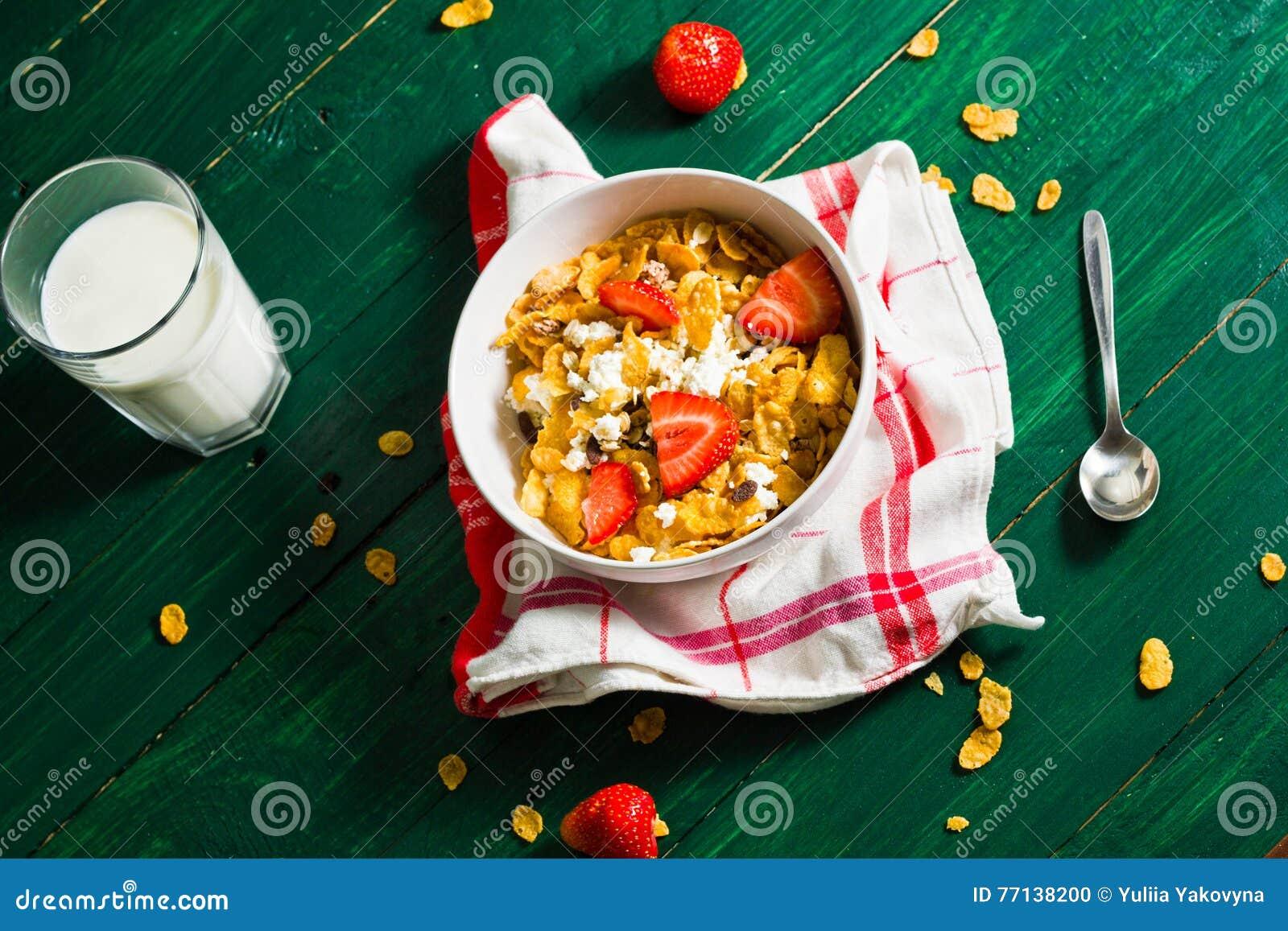 Café da manhã de flocos da farinha de aveia e de milho com leite e morangos