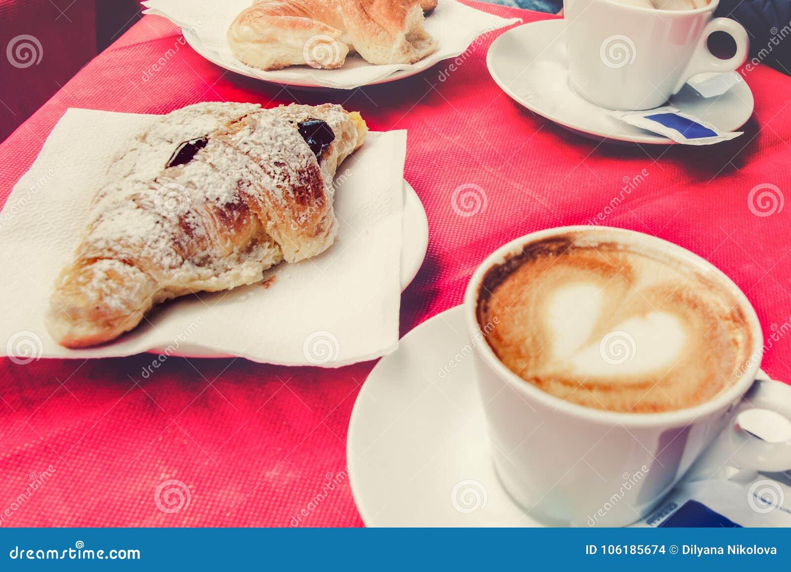 Café da manhã da manhã em um restaurante italiano - o croissant e uma xícara de café com um coração deram forma à espuma