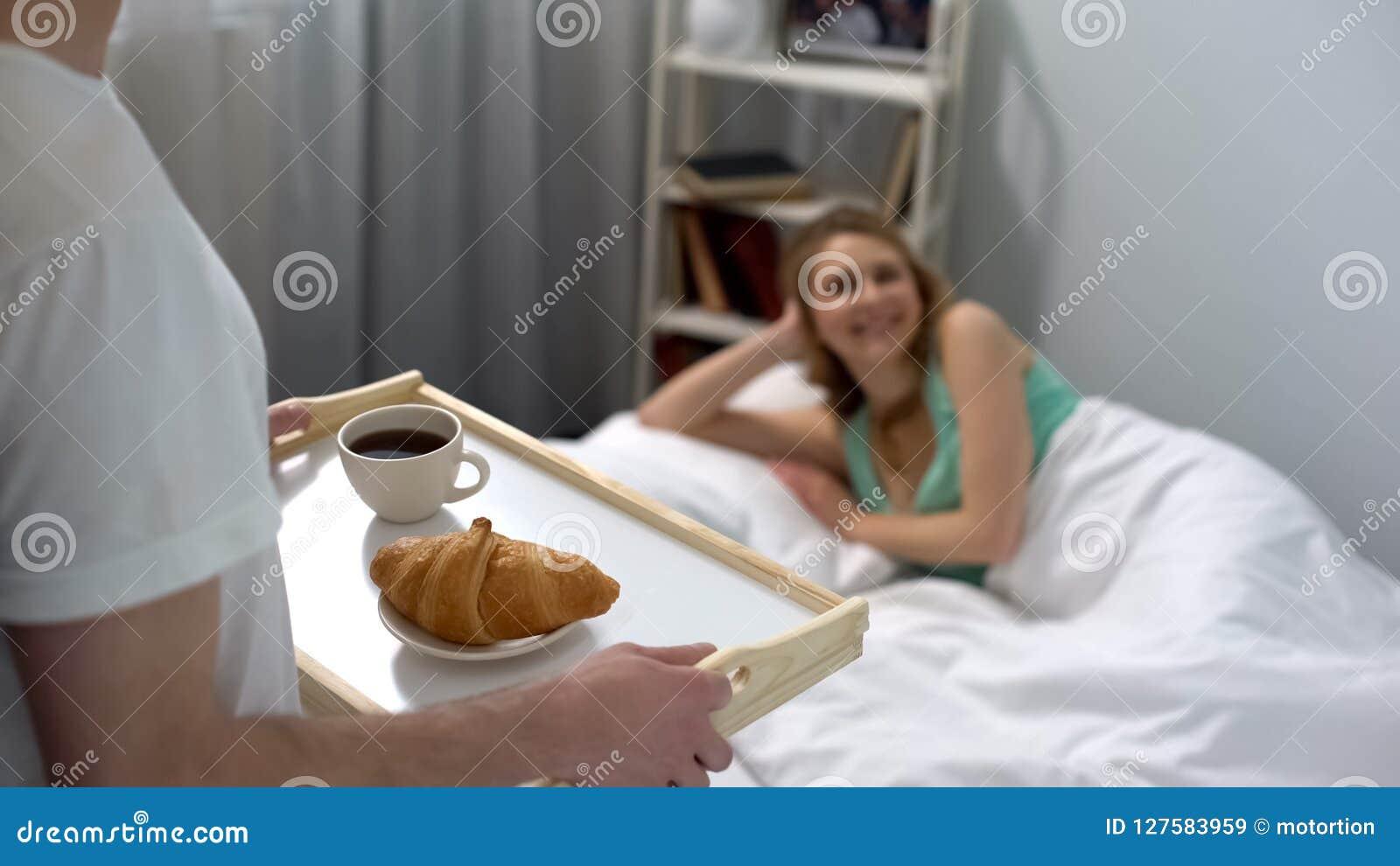 Café da manhã levando do marido loving na cama, café com o croissant na bandeja, romance