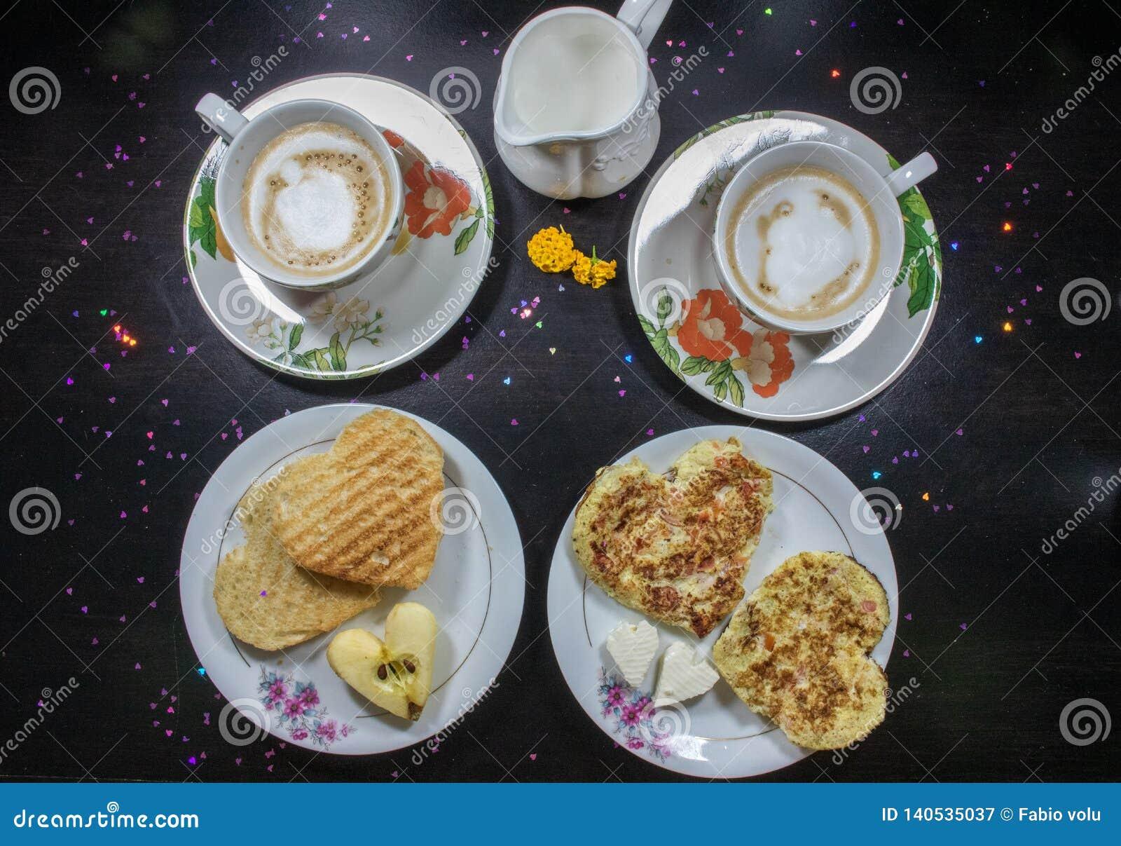 Café da manhã no dia de Valentim - queijo fritado do omelete, do pão, do maçã e o branco na forma de um coffe e de um leite do co