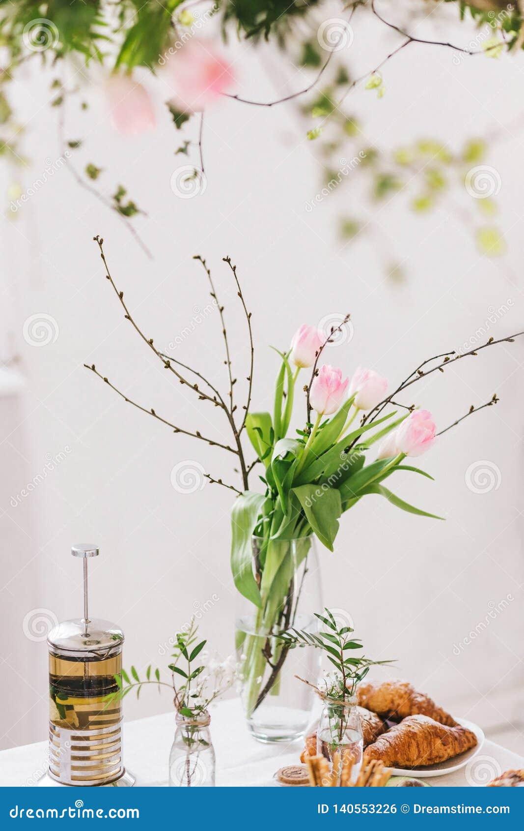 Café da manhã saboroso com croissant, torta, chá na tabela Ramalhete das tulipas