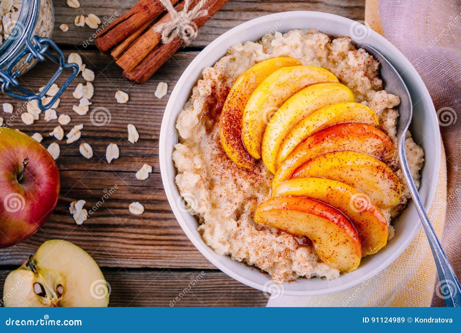 Café da manhã saudável: bacia da farinha de aveia com pêssegos, canela e mel caramelizados