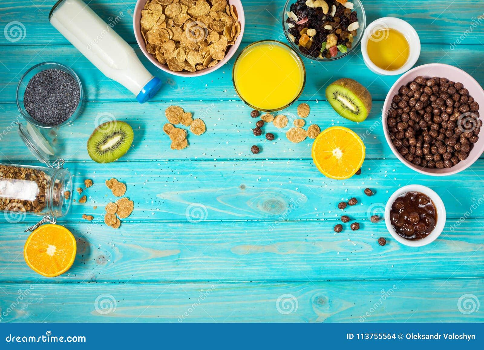 Café da manhã saudável com a bacia de cereal, de suco de laranja, de granola, de leite, de doce e de frutos no fundo de madeira a