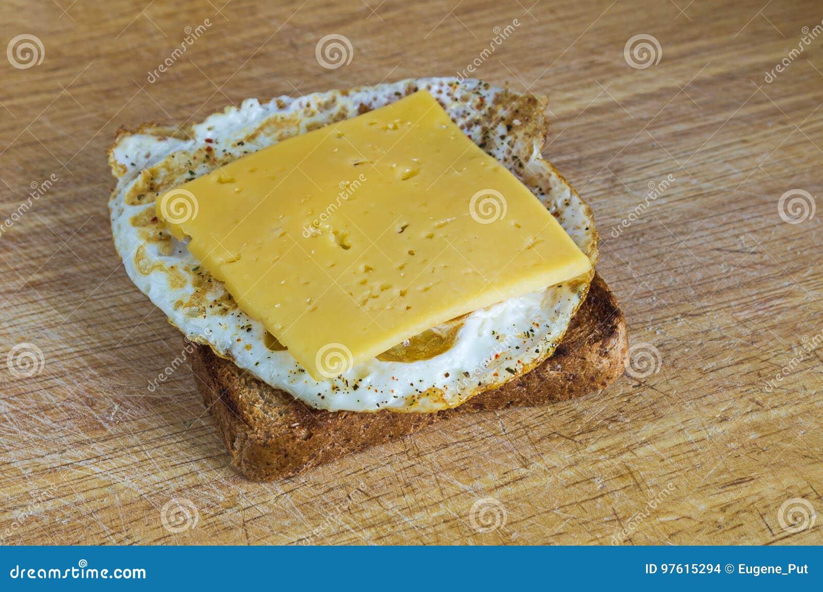 Café da manhã saudável: ovo frito em um brinde inteiro do trigo