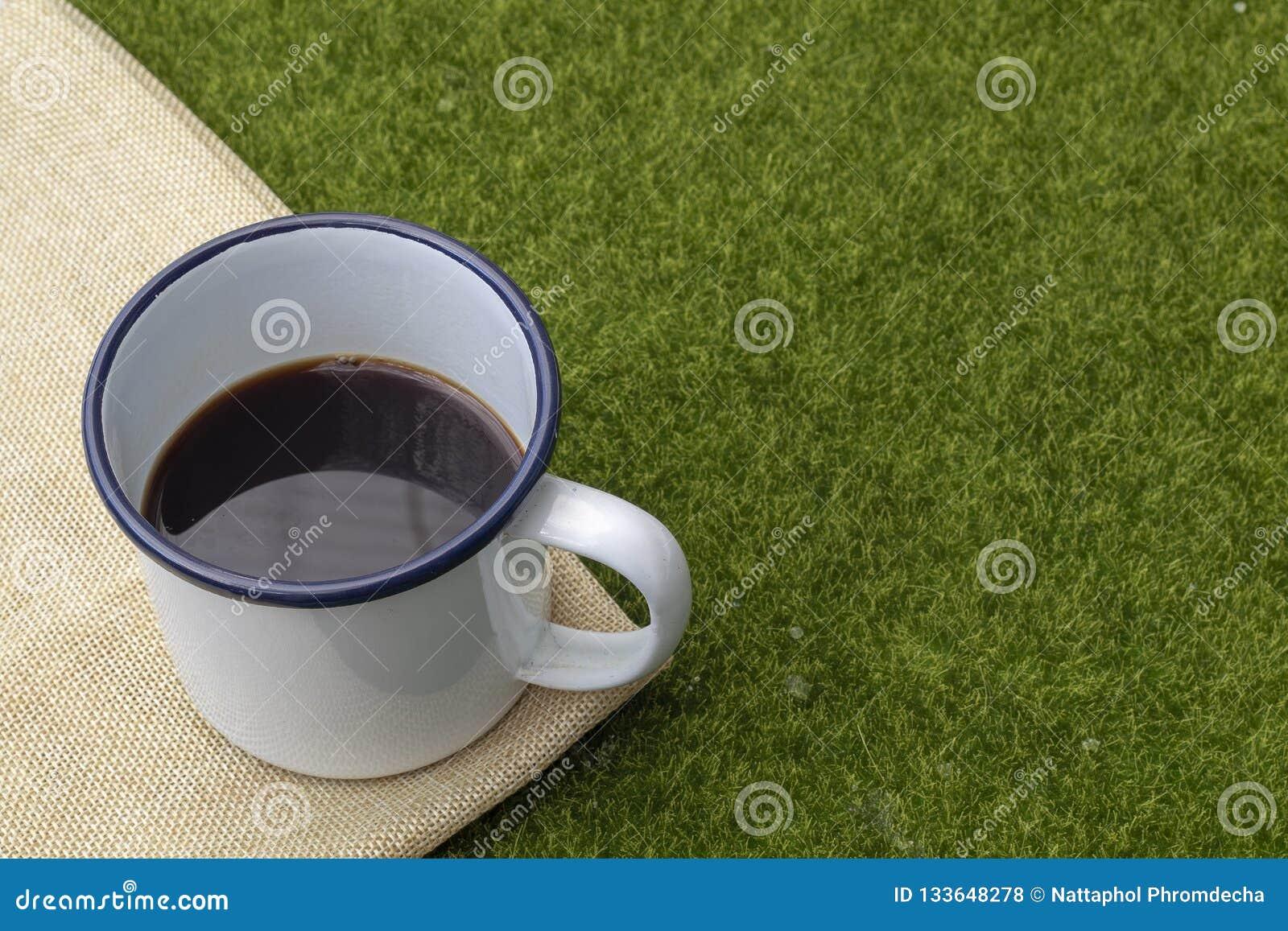 Café dans la tasse blanche de bidon sur le fond d herbe