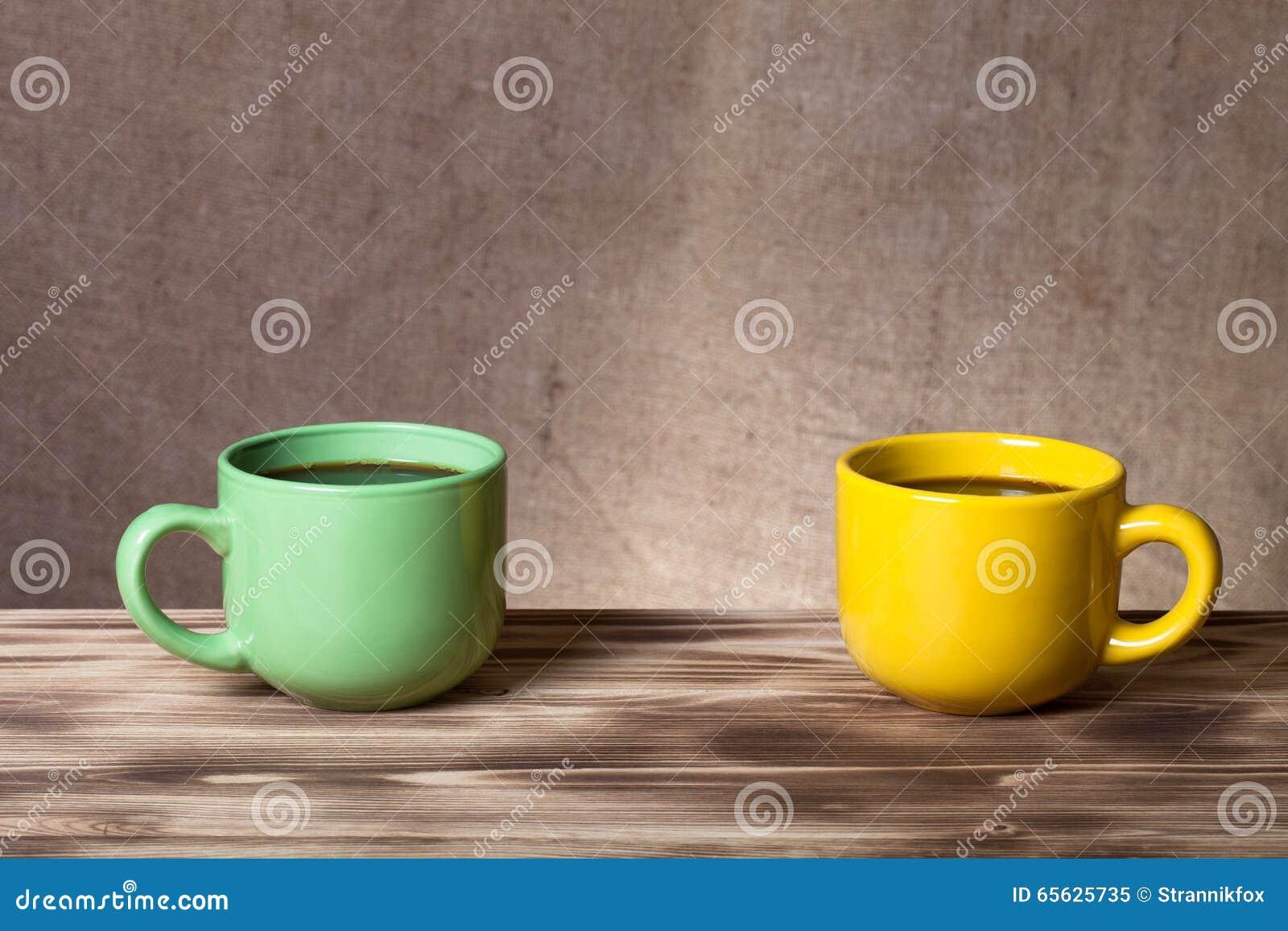 Café dans la tasse sur la table en bois vis-à-vis d un backgr defocused de toile de jute