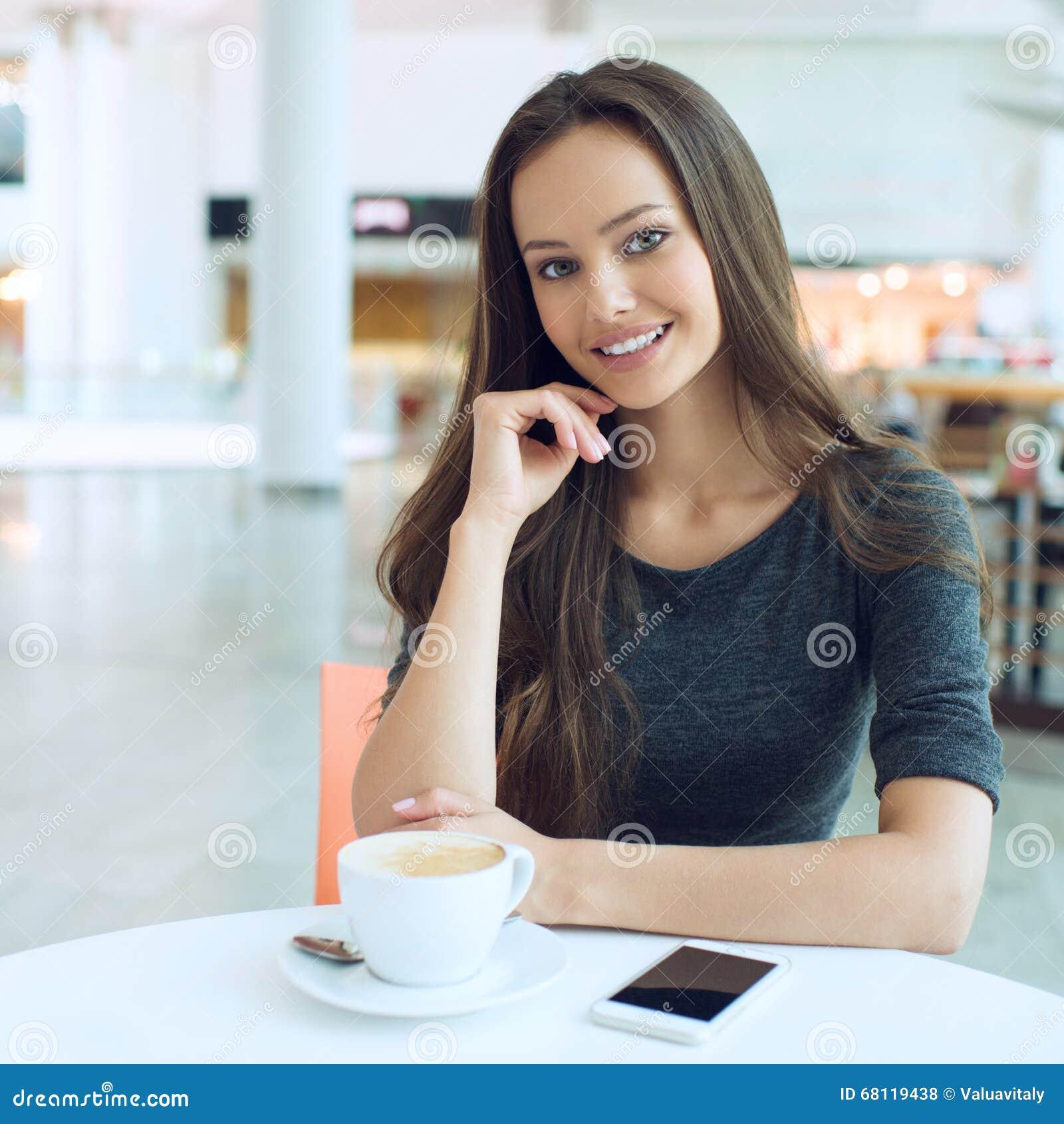 Café de consumición de la mujer por la mañana en el foco suave del restaurante