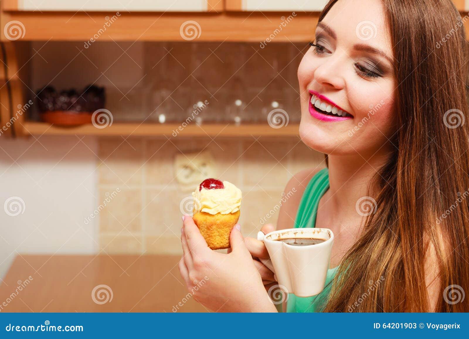Café de consumición de la mujer y consumición de la torta deliciosa
