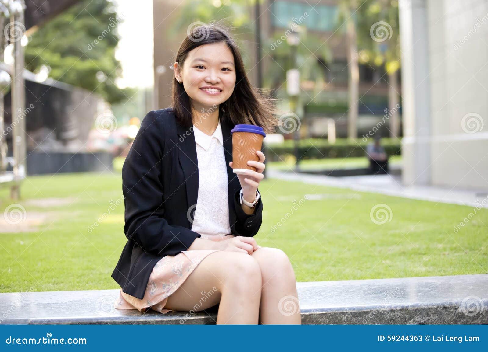Café de consumición del ejecutivo de sexo femenino asiático joven y usar la PC del ordenador portátil