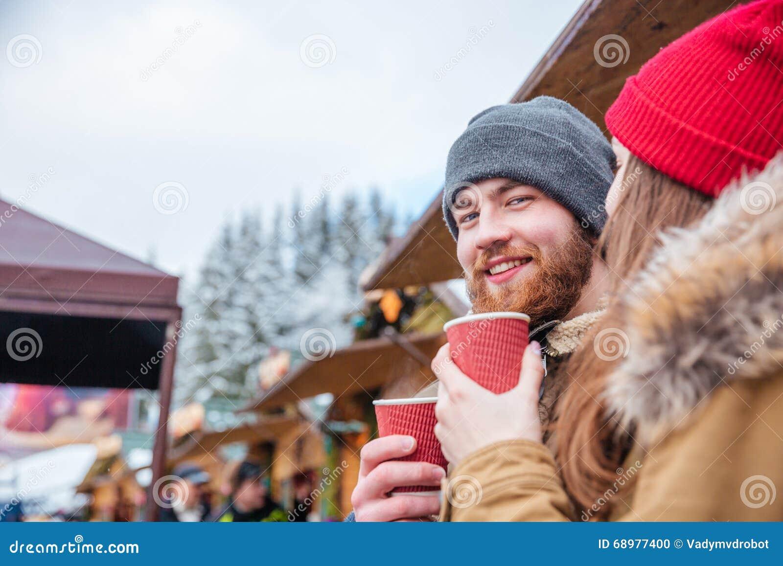 Café de consumición del hombre barbudo al aire libre con su novia