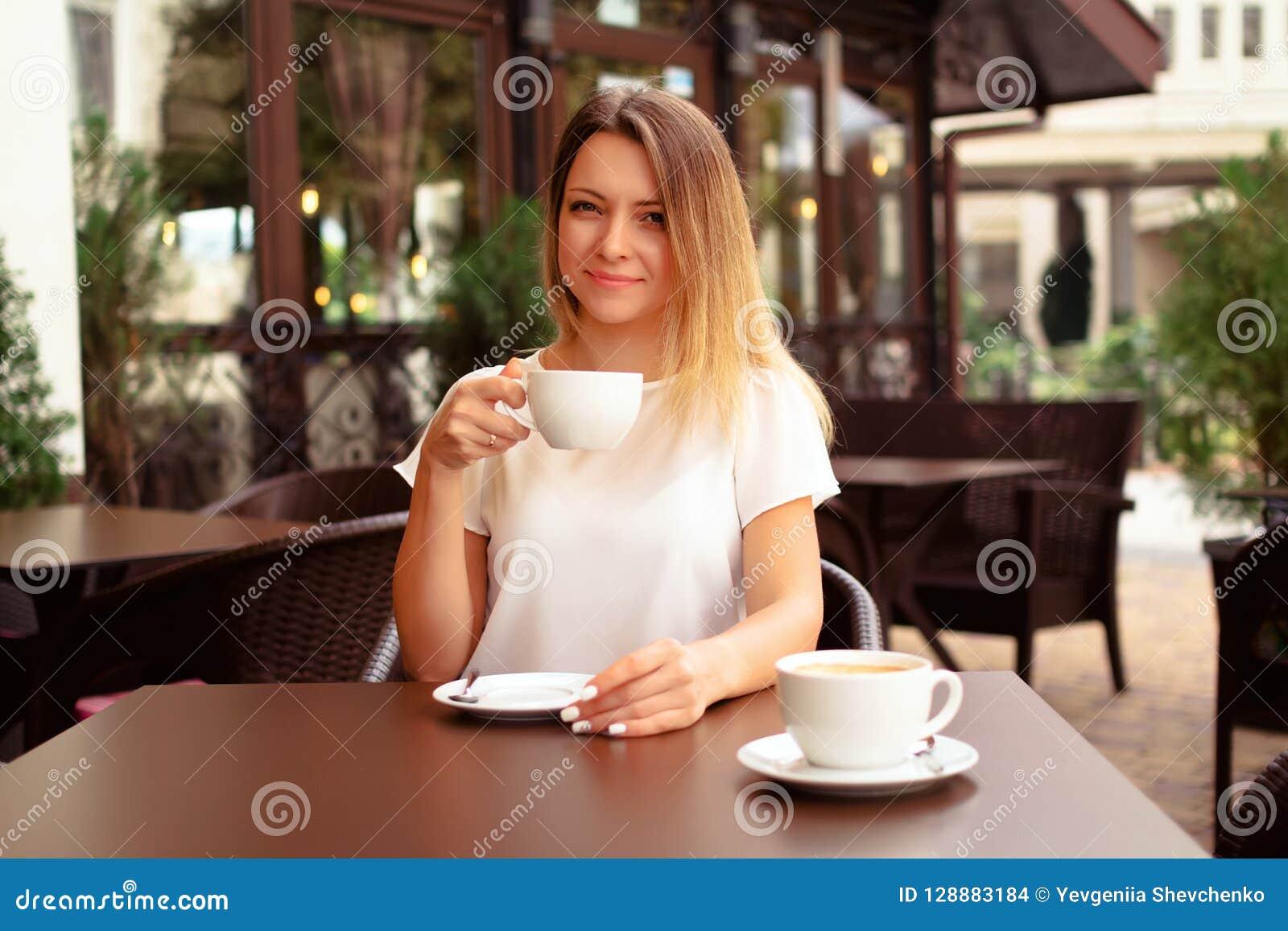Café de consumición de la mujer hermosa en el café