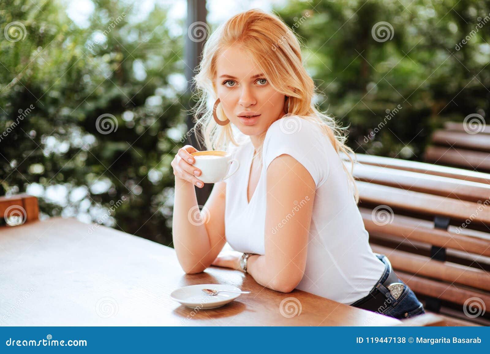 Café de consumición de la mujer hermosa en un café