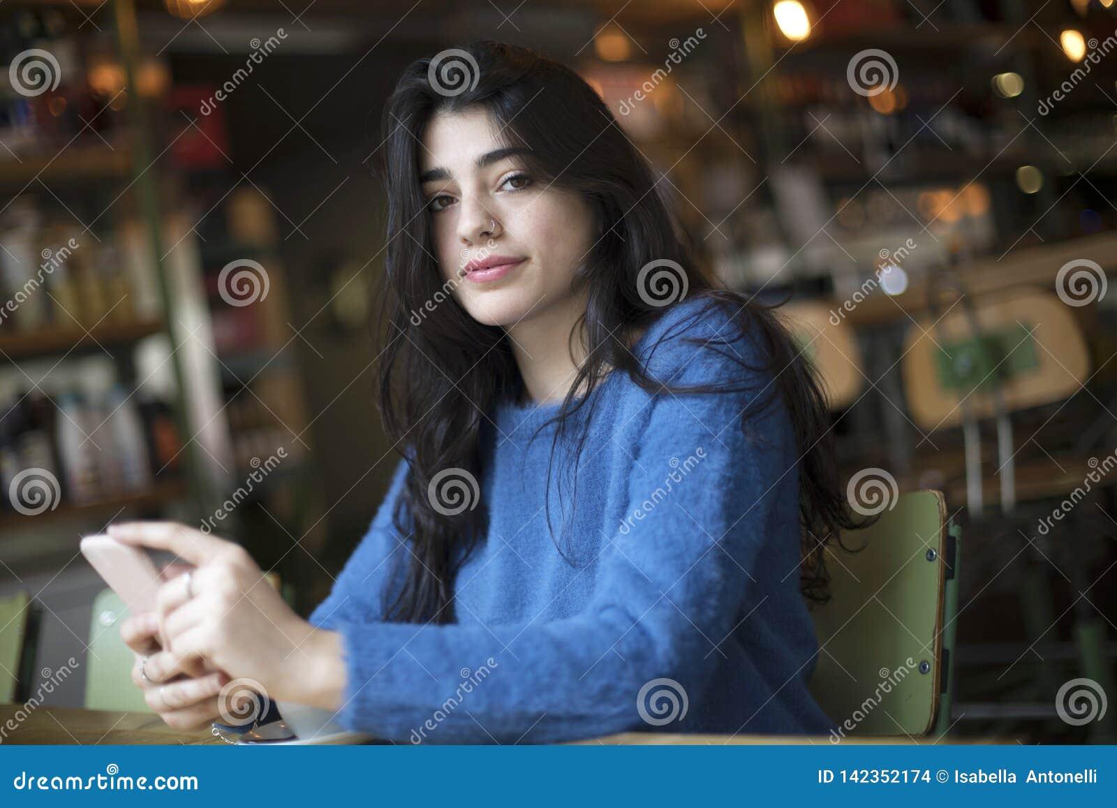 Café de consumición de la mujer hermosa joven y utilizar su sentarse del smartphone interior en café urbano Forma de vida de la c