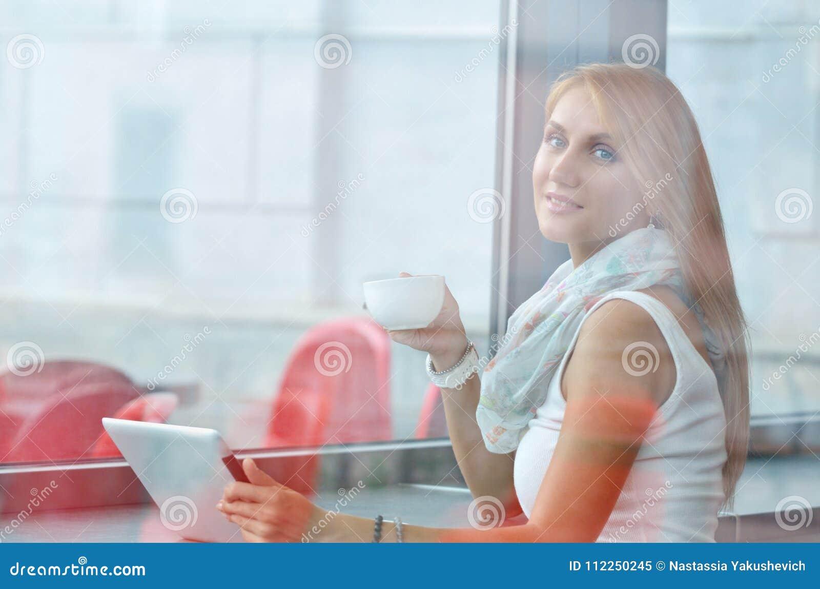 Café de consumición de la mujer por la mañana en el restaurante