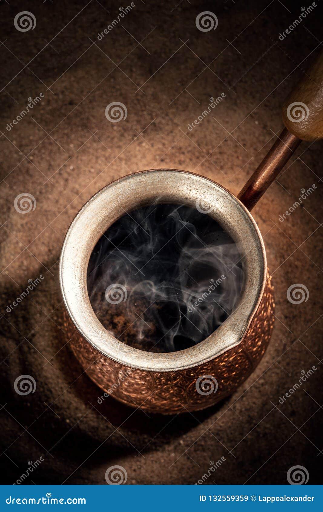 Café de ebullición en el café turco de cobre que prepara el pote