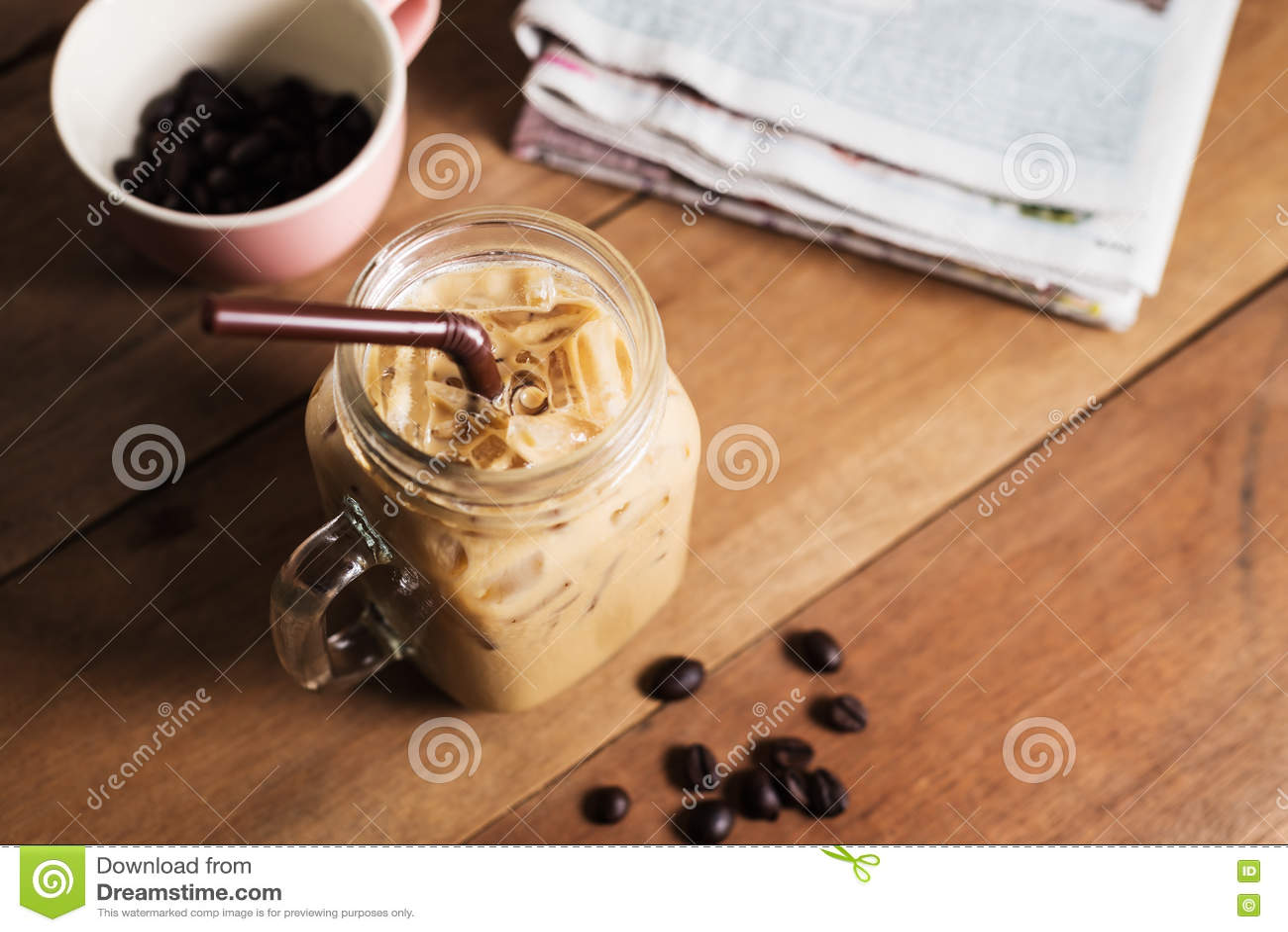 Café de gelo com leite e jornal na tabela