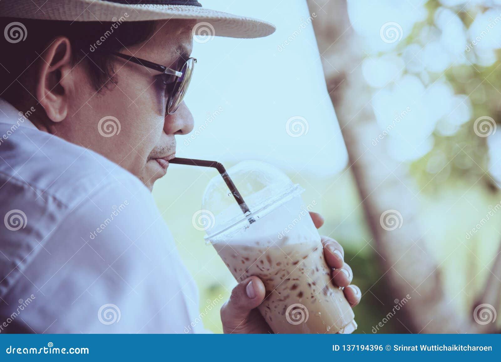 Café de hielo asiático casual de la bebida del hombre feliz en naturaleza