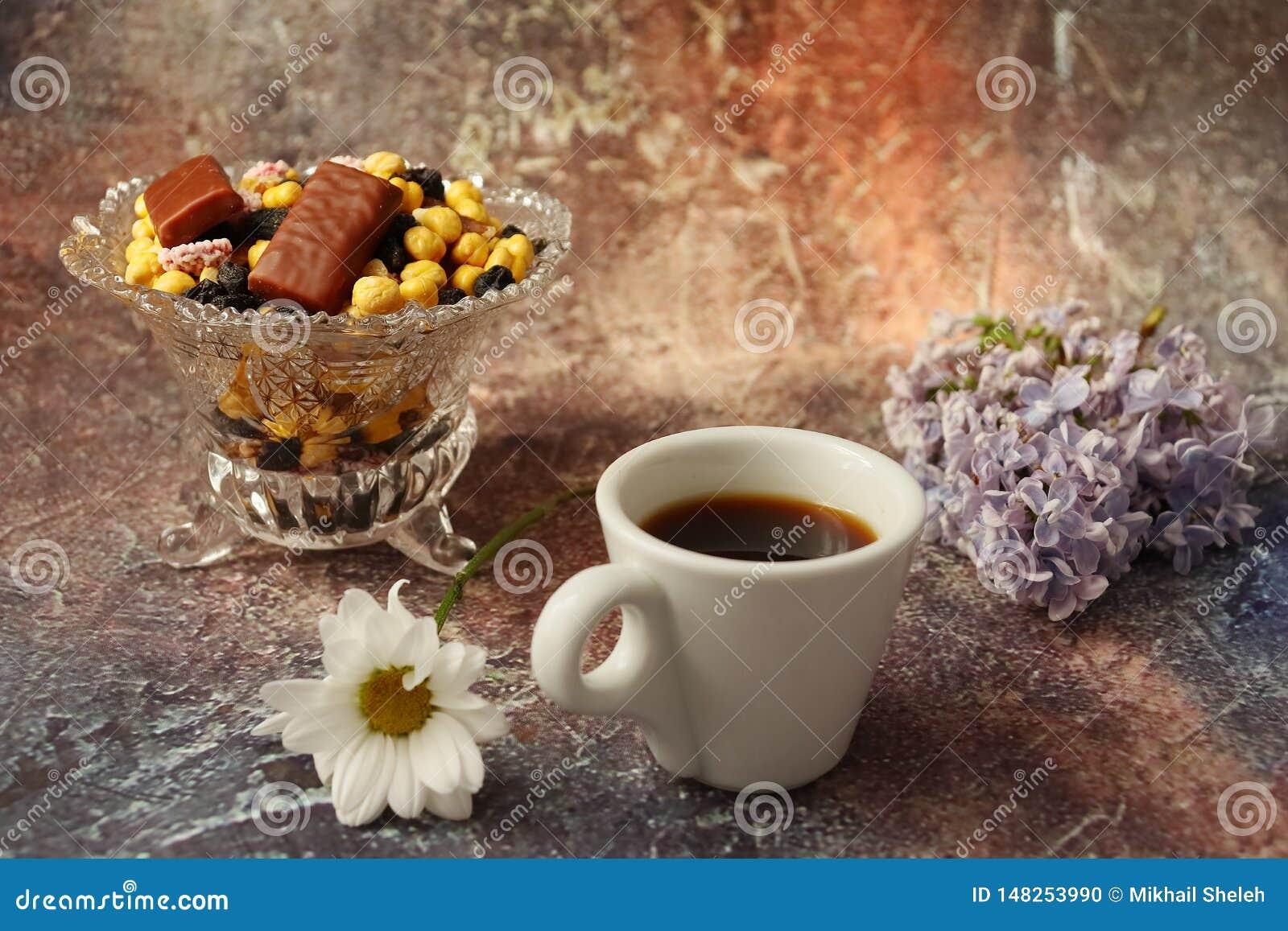 Café de la mañana a toda prisa: una taza de café, de flores en un florero, de frutas secadas y de dulces en un florero, una vela