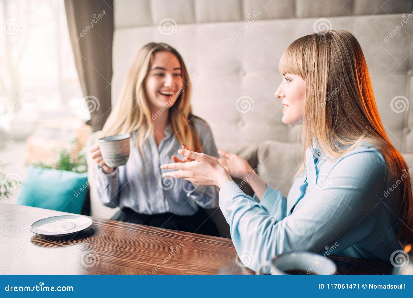 Café de sourire de deux boissons d amies en café