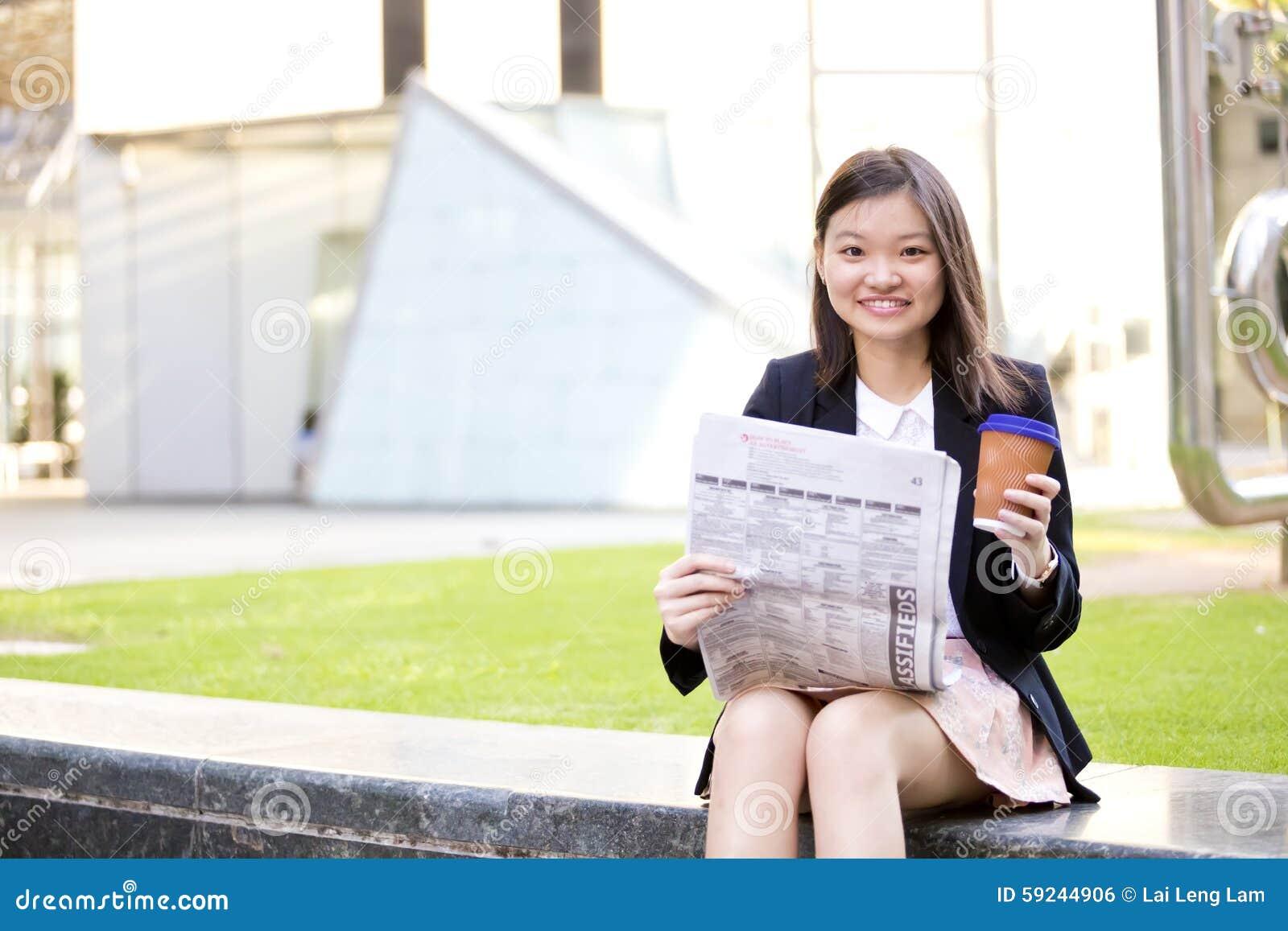 Café del ejecutivo de sexo femenino asiático joven y periódico de consumición de la lectura