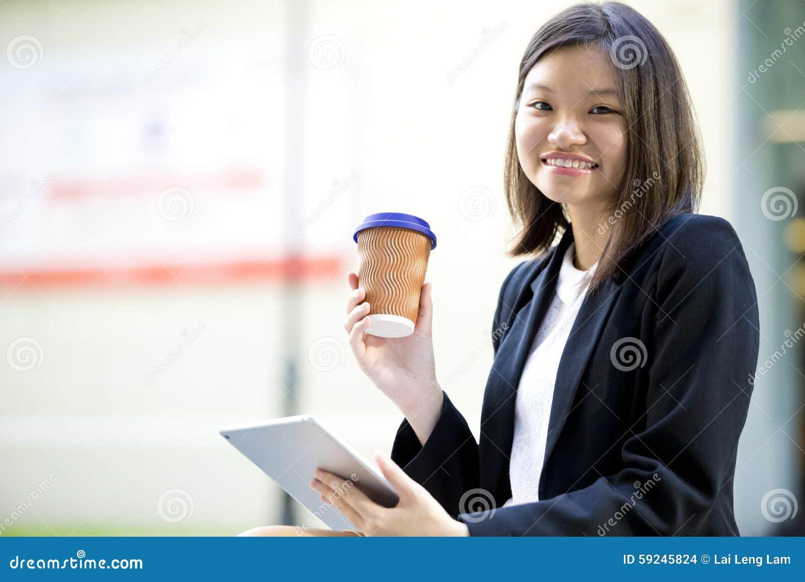 Café del ejecutivo de sexo femenino asiático joven y tableta de consumición con