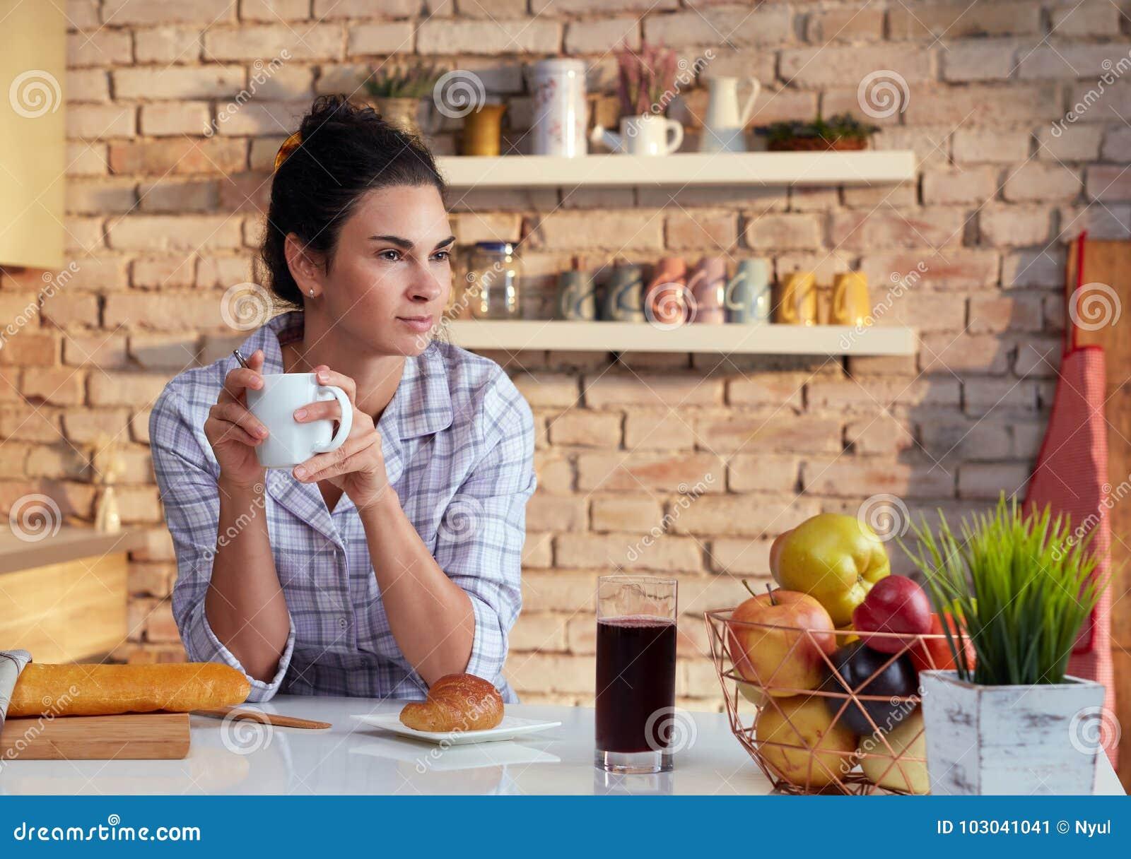 Café do café da manhã das bebidas da jovem mulher no pyjama