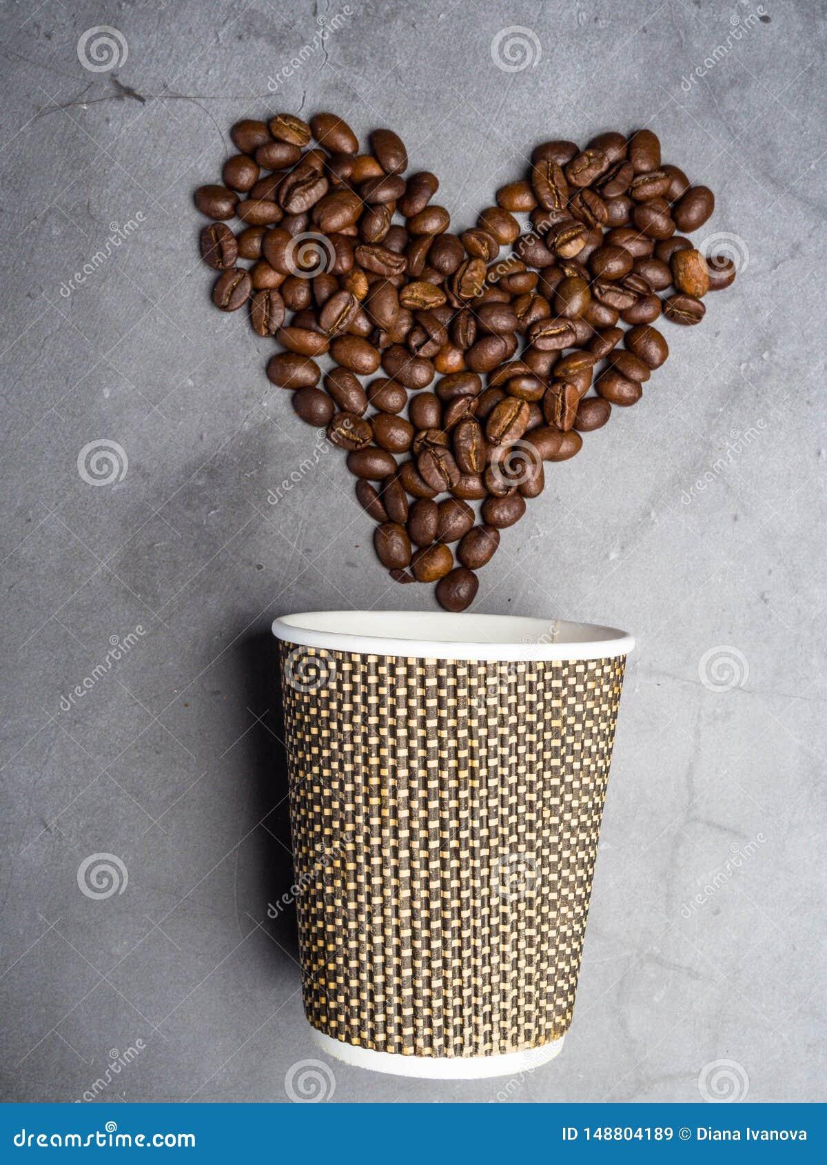 Caf? do papel da vista superior a ir copo e cora??o feitos dos feij?es de caf?, espa?o da c?pia, fundo cinzento