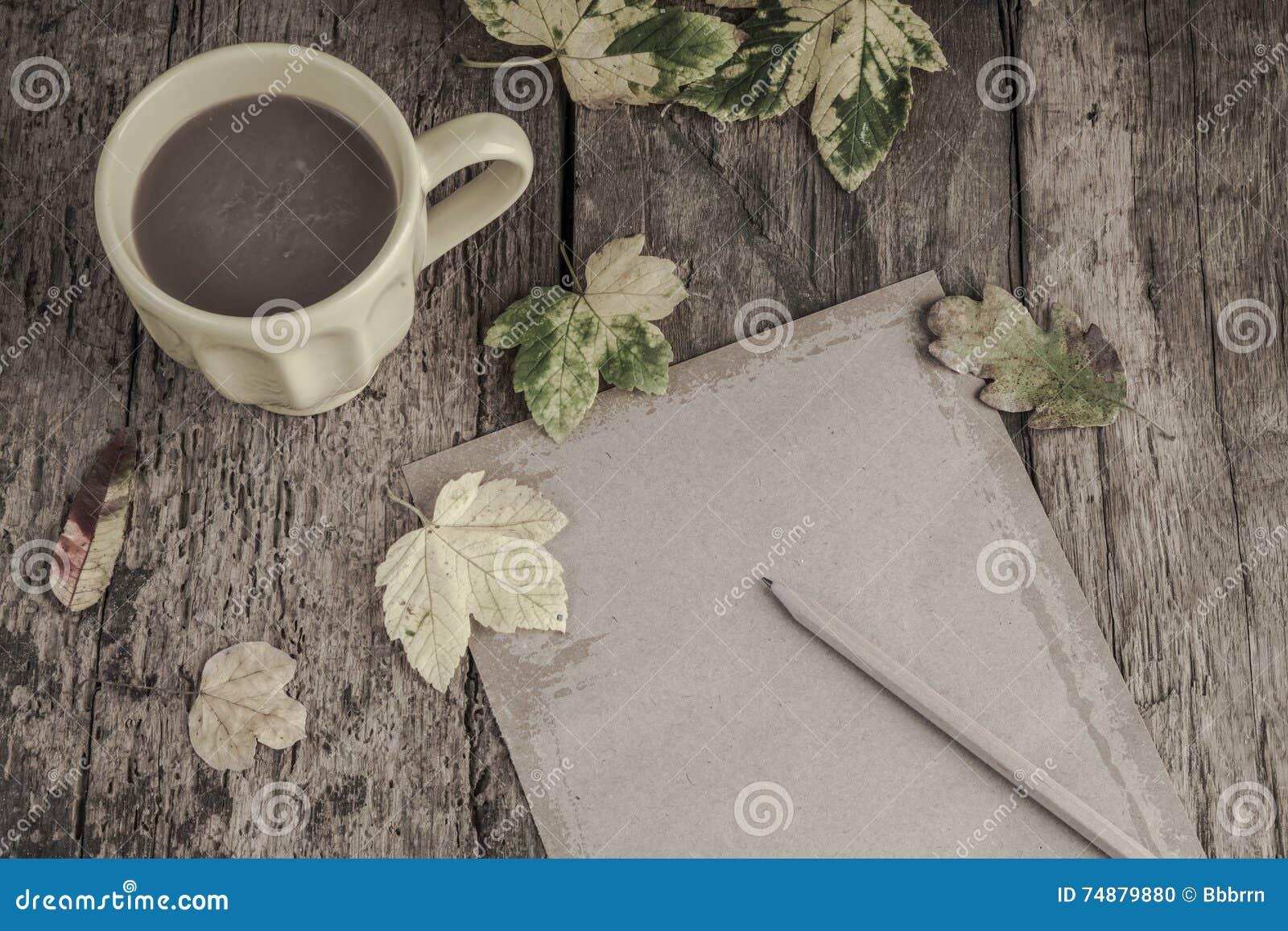 Café e caderno na tabela de madeira decorada com folhas de outono