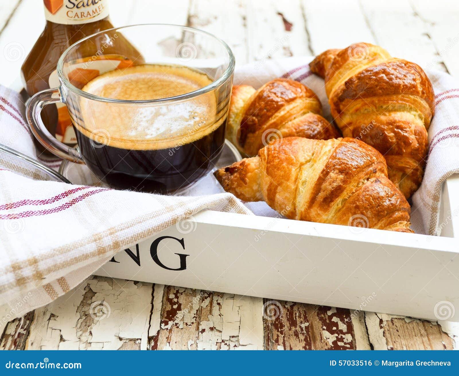 Café e croissant na bandeja de madeira