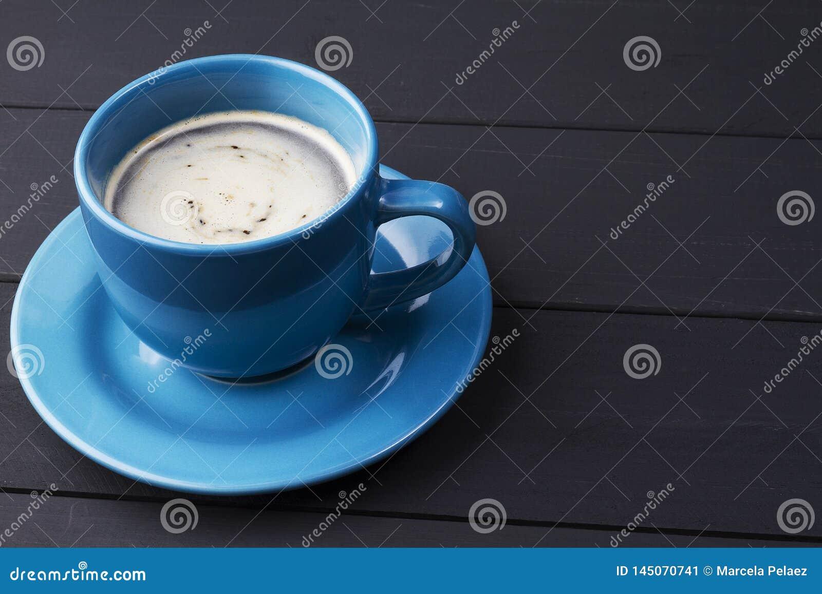 Café en taza azul con hacer juego el plato en fondo de madera negro