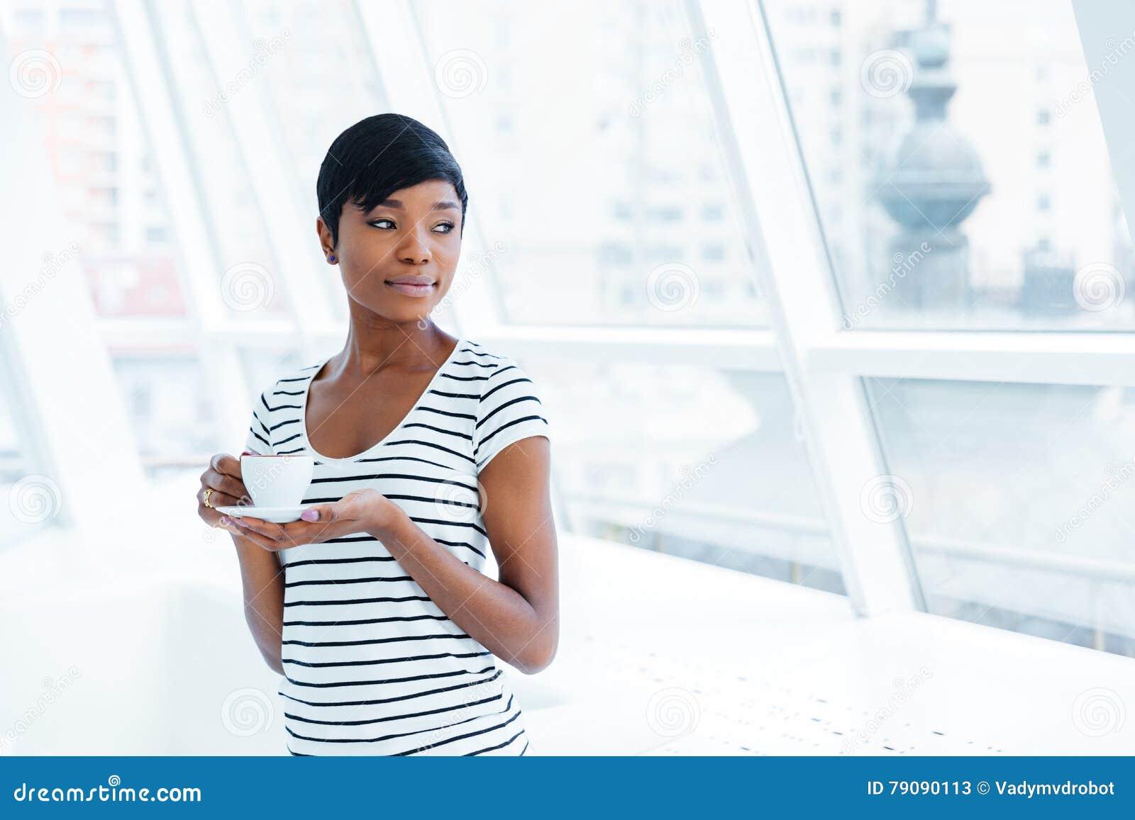 Café estando e bebendo da mulher de negócios nova afro-americano bonita