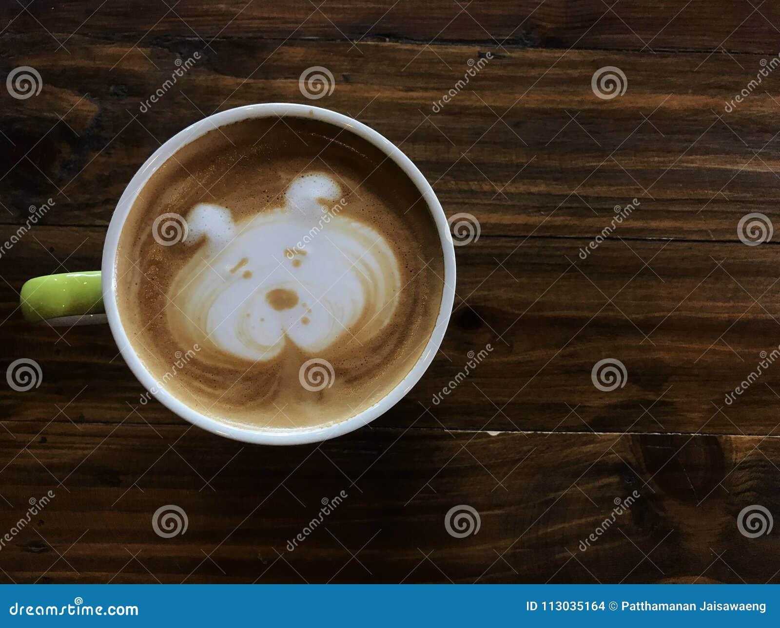 Café lindo del arte del latte de la cara del perro en la taza blanca en la tabla de madera