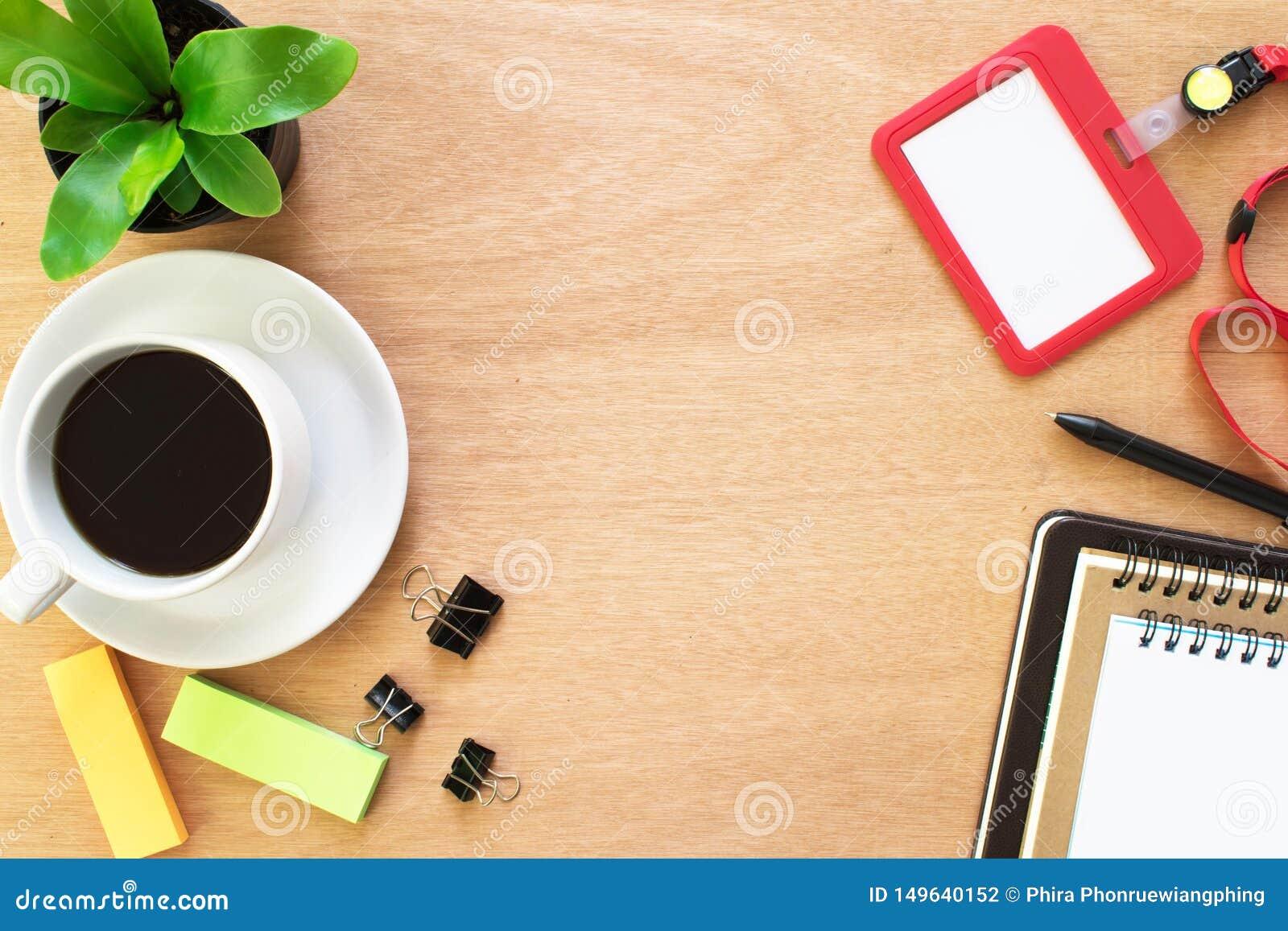 Café, livro, clipe, lápis, cartão do empregado, post-it e potenciômetro da árvore na mesa de madeira marrom rústica Espaço de tra